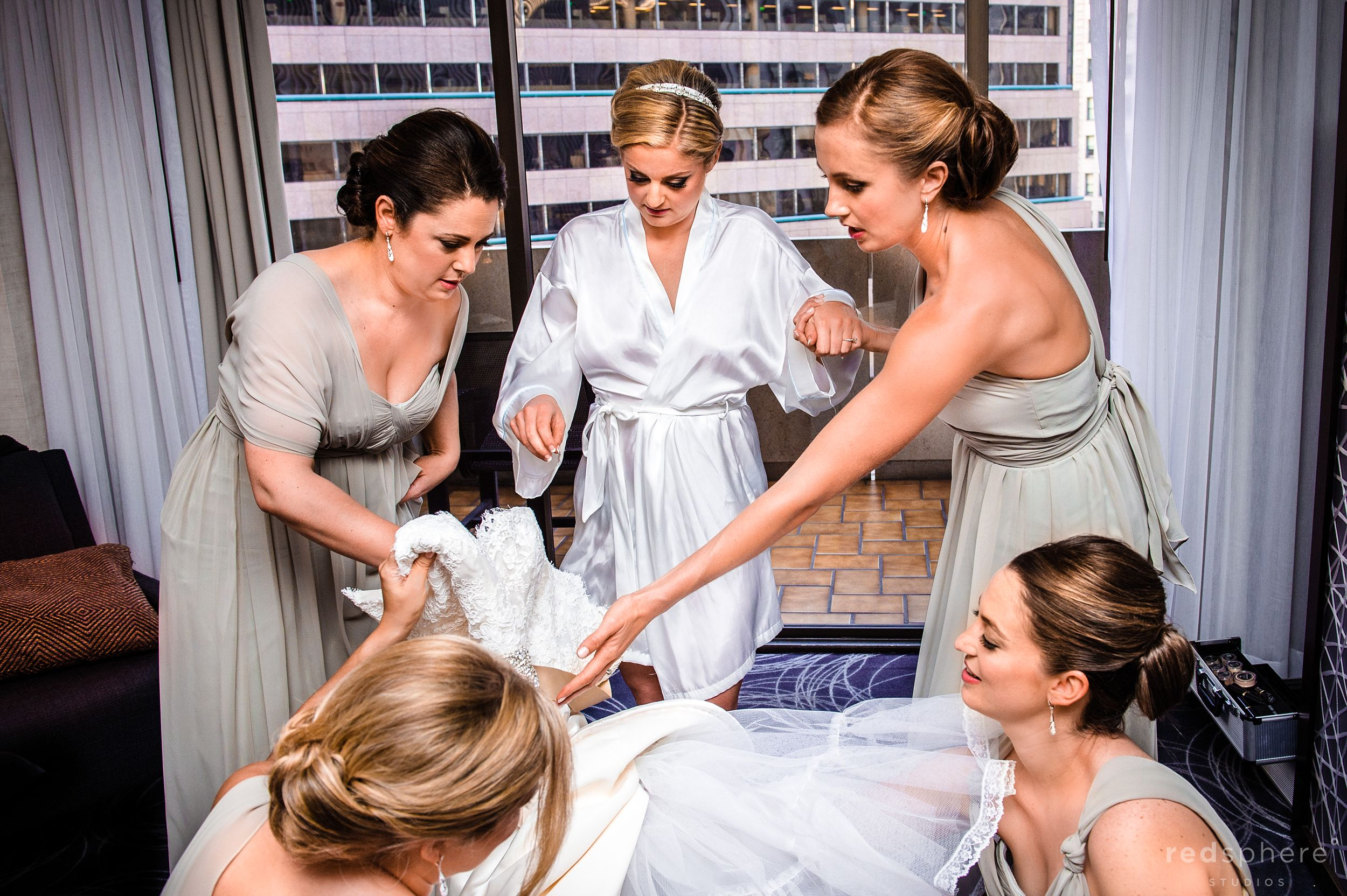 Bridesmaids' Help Bride Get Fitted Into Her Wedding Gown at City Club San Francisco