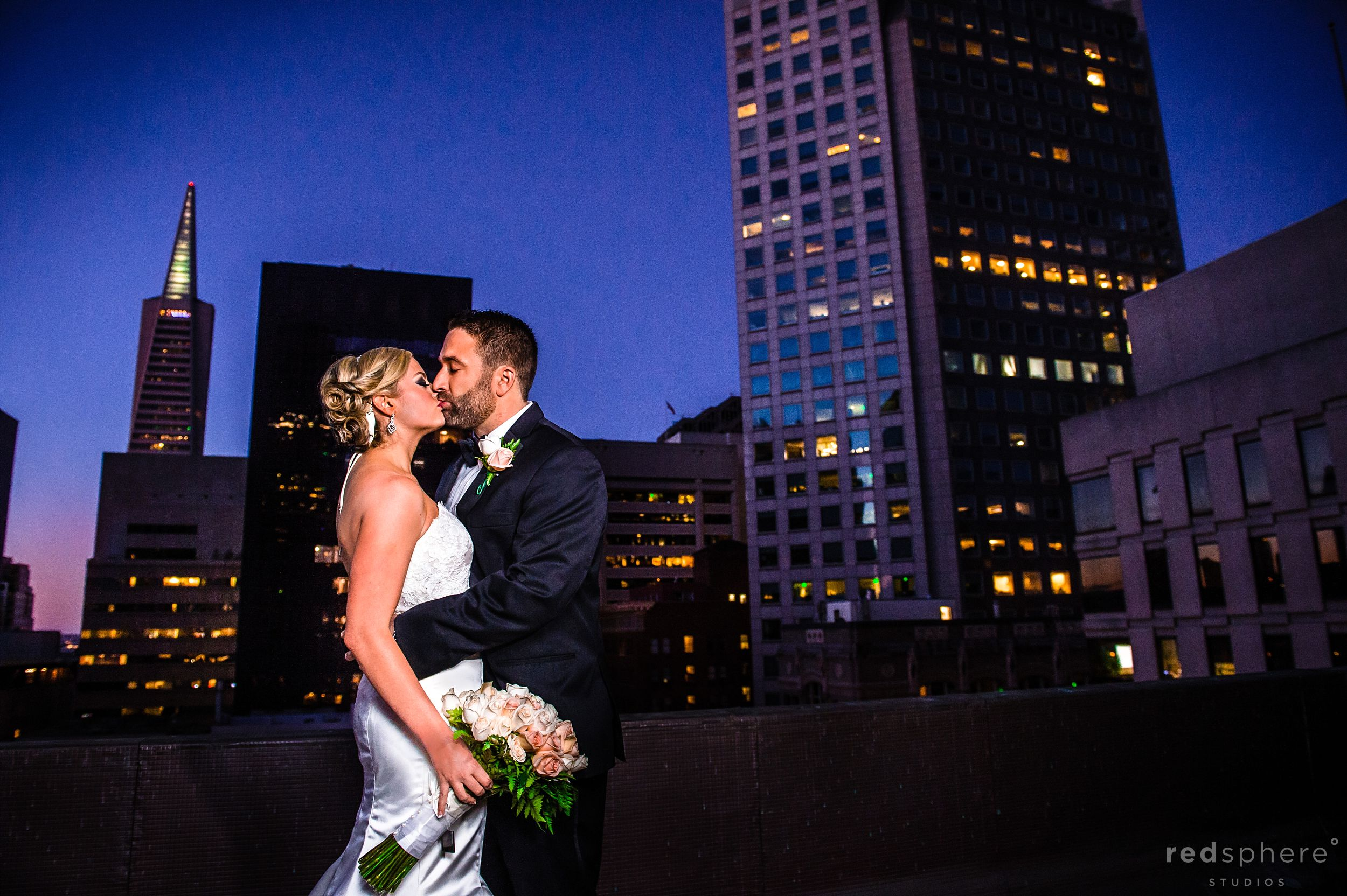 Bride and Groom Kiss With San Francisco Skyline lit up Behind Them
