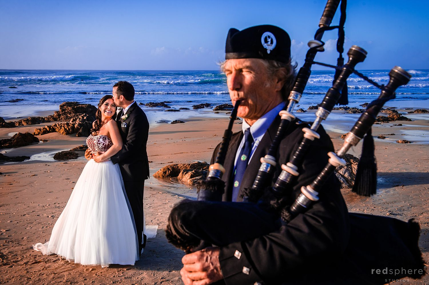 Groom Kisses Bride While Bagpipes Play at The Inn at Spanish Bay Wedding