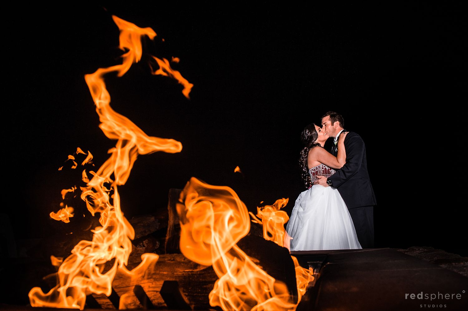 Bride and Groom Kiss Next to a Fireplace