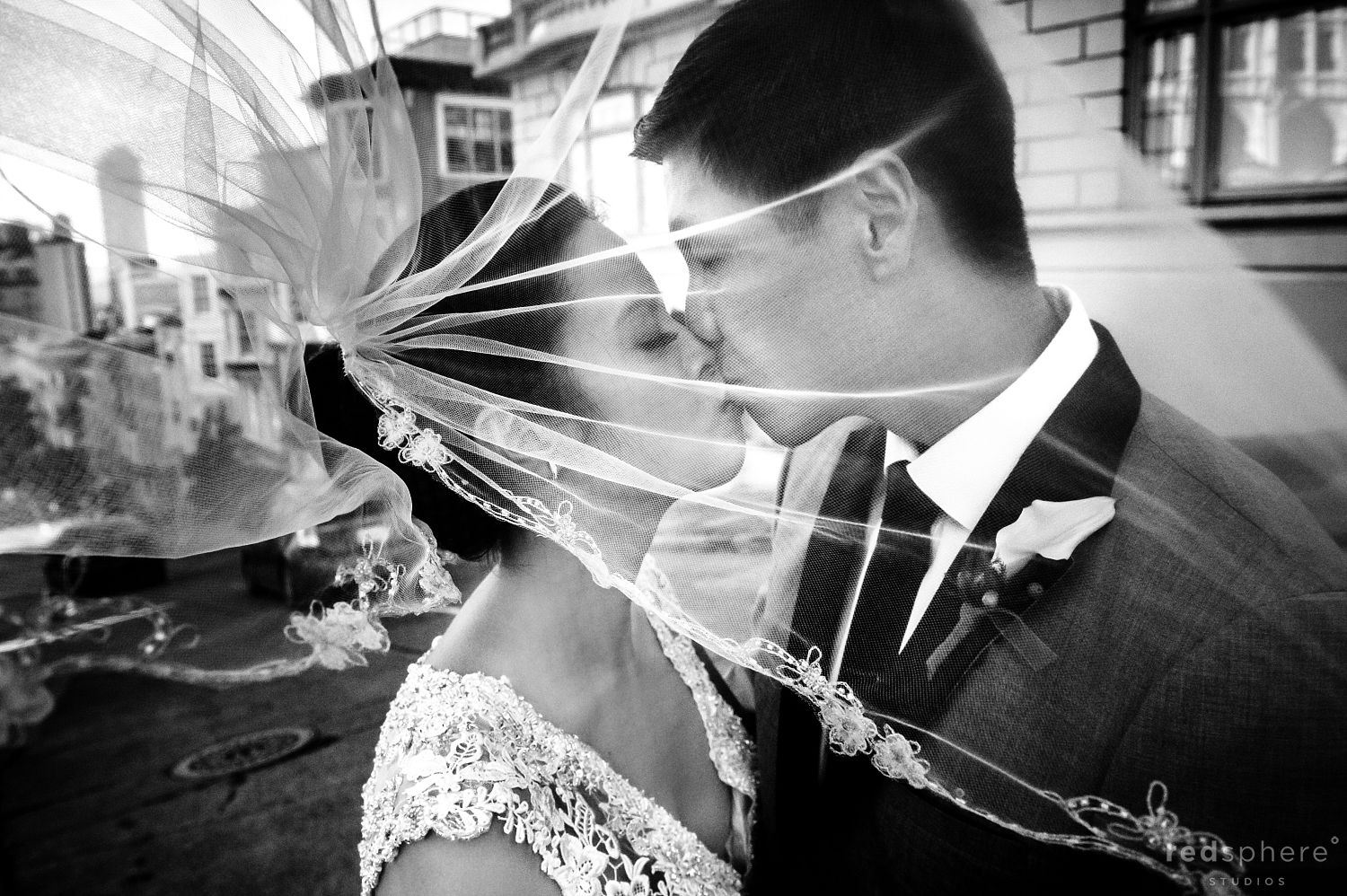 Bride and Groom Kiss as her Veil Flies From the Wind