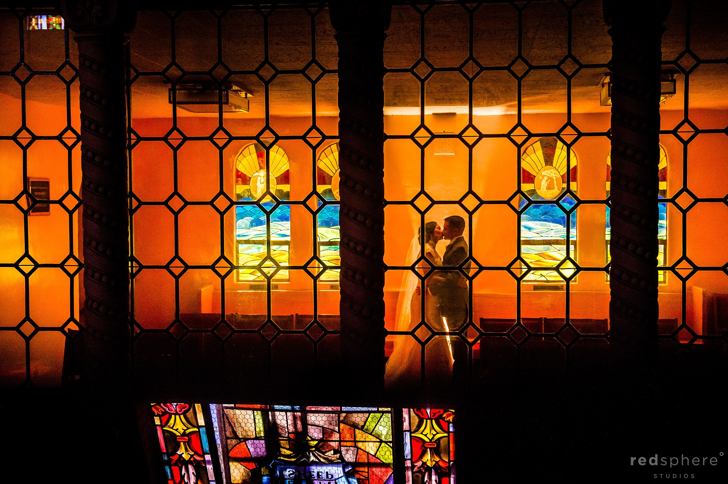 Bride and Groom Kiss Through Stain Glass at St. Gregory Catholic Church