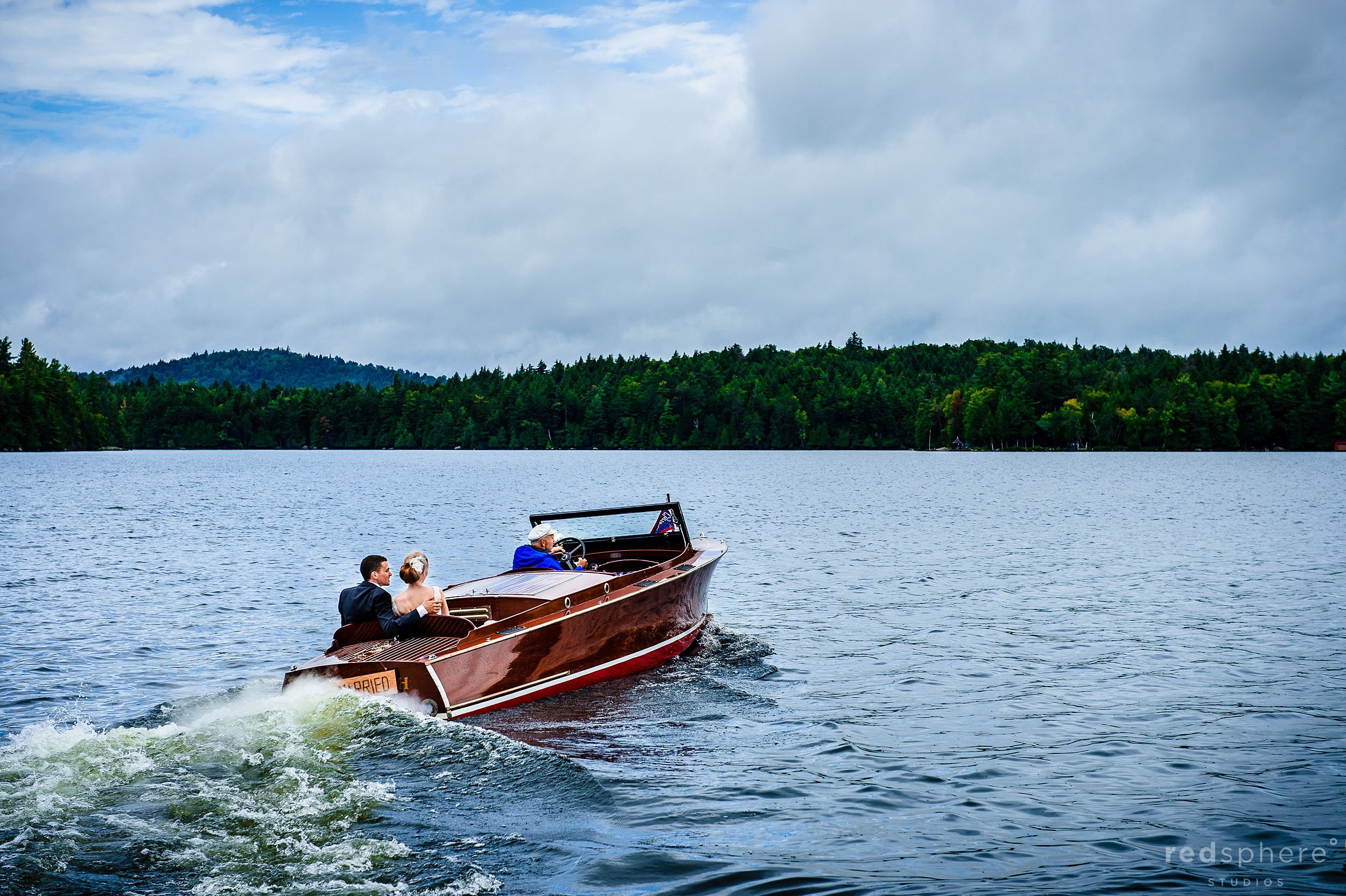 Bride and Groom Ride off on a Boat at Saranac Lake, New York
