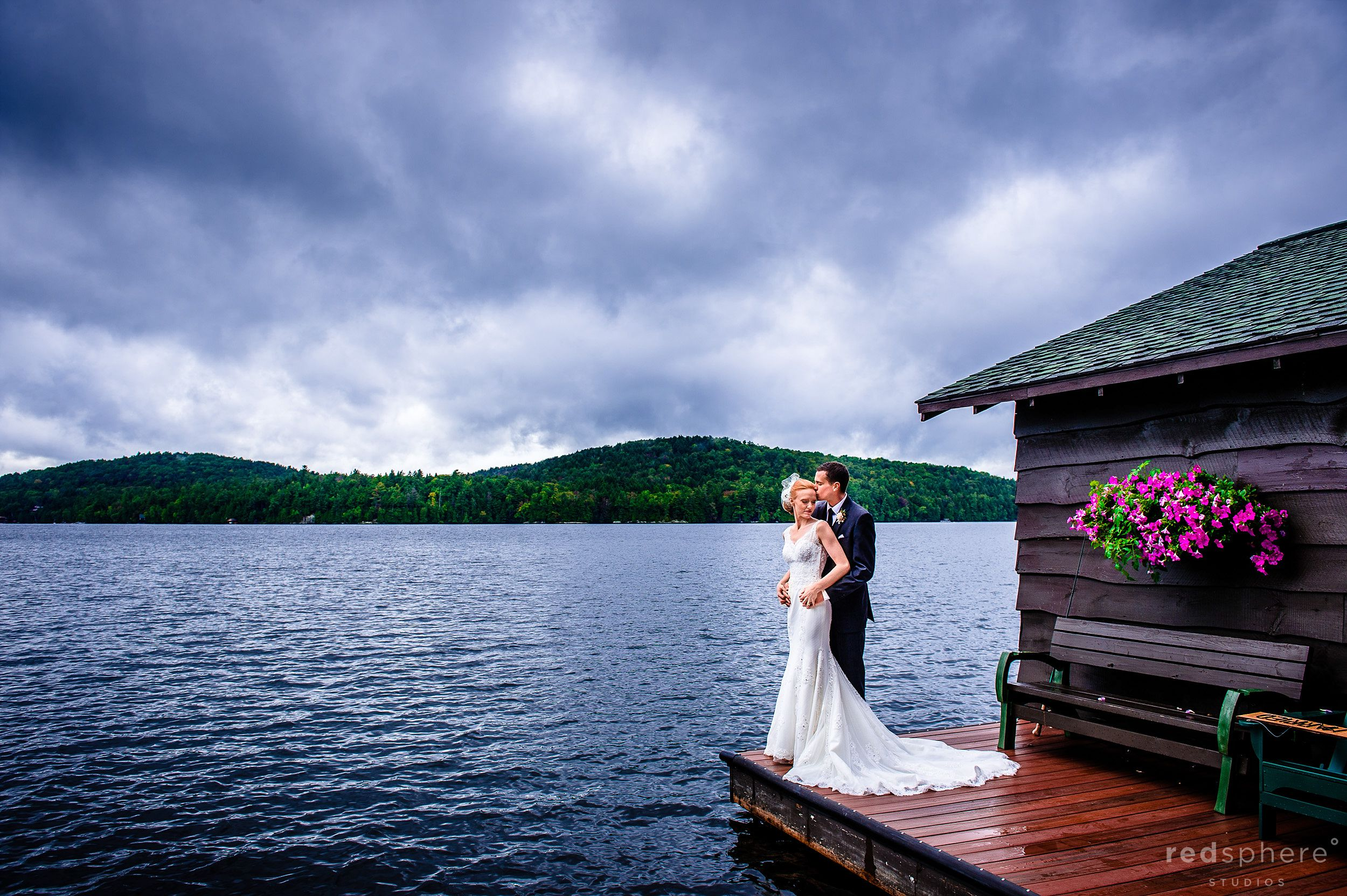 Groom Hugging Bride on Saranac Lake Dock New York