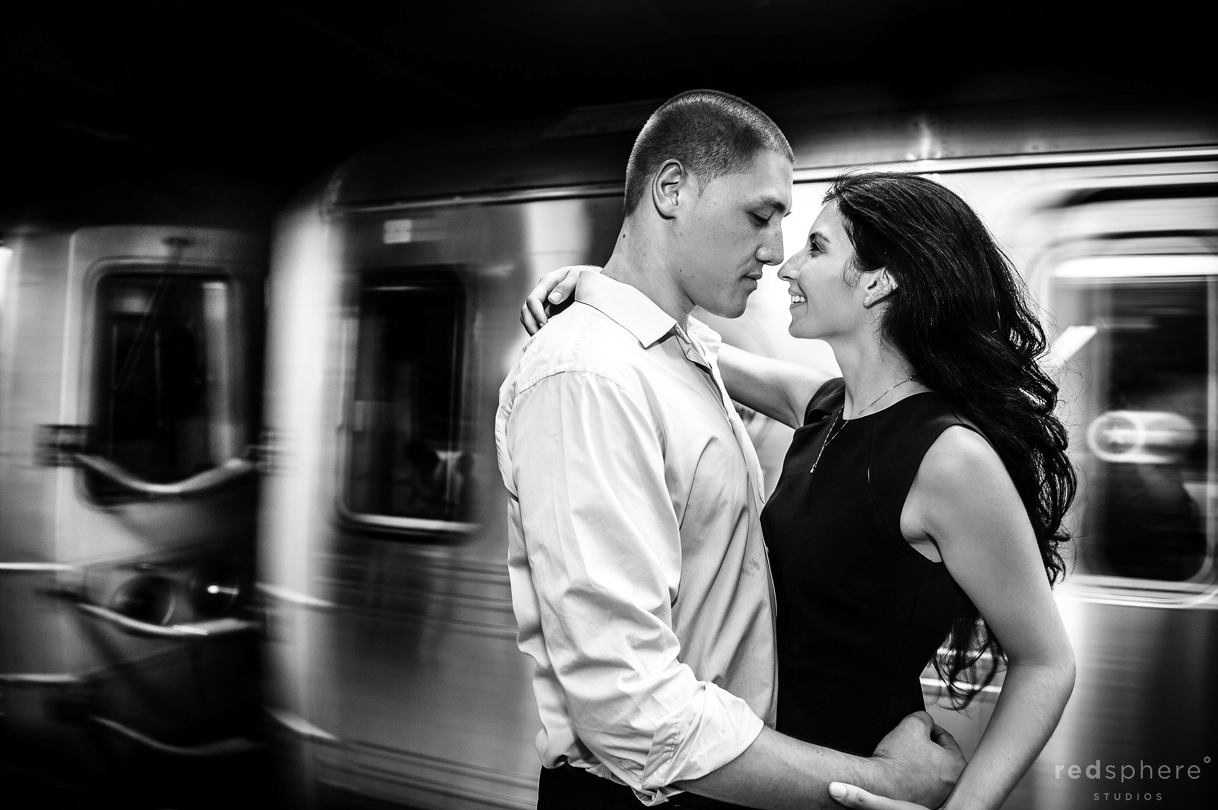 Couple Embracing While Subway Passes, Black and White Engagement