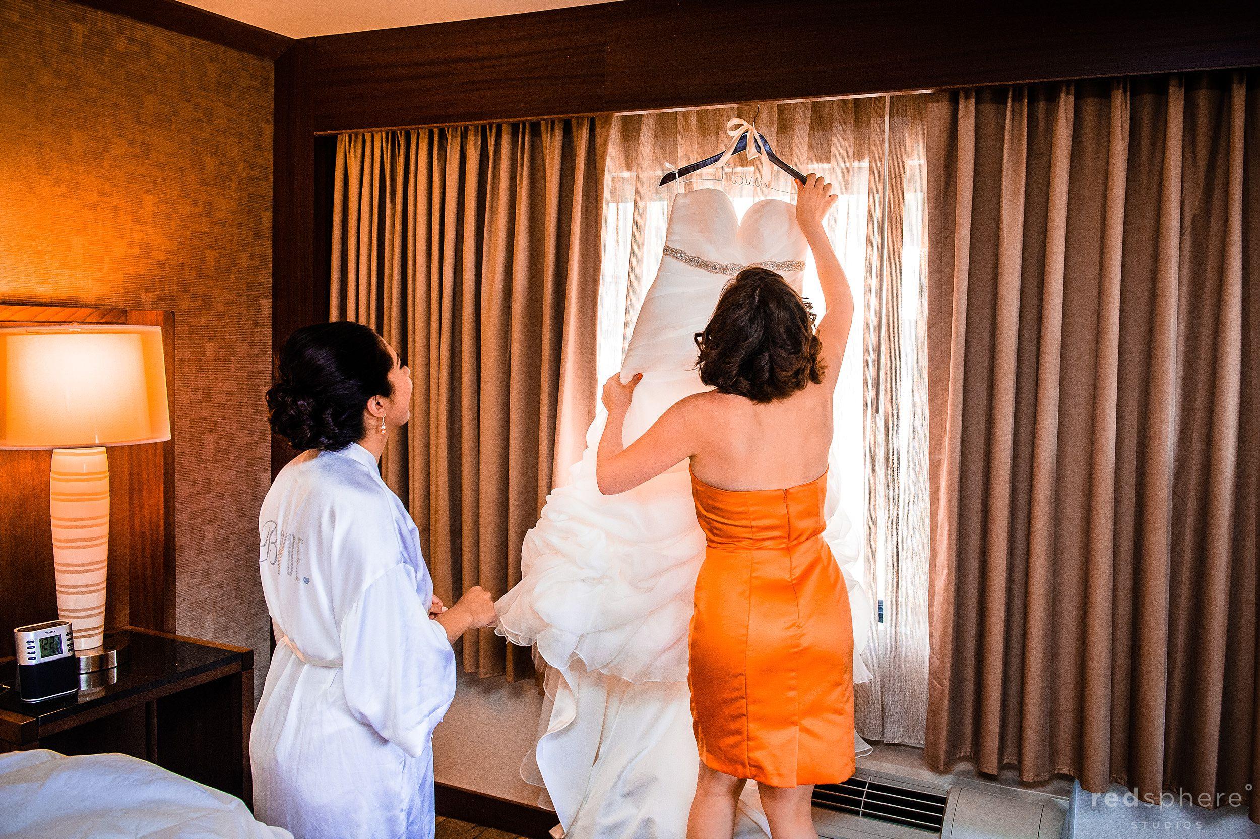 Bridesmaid and Bride Grab Wedding Gown