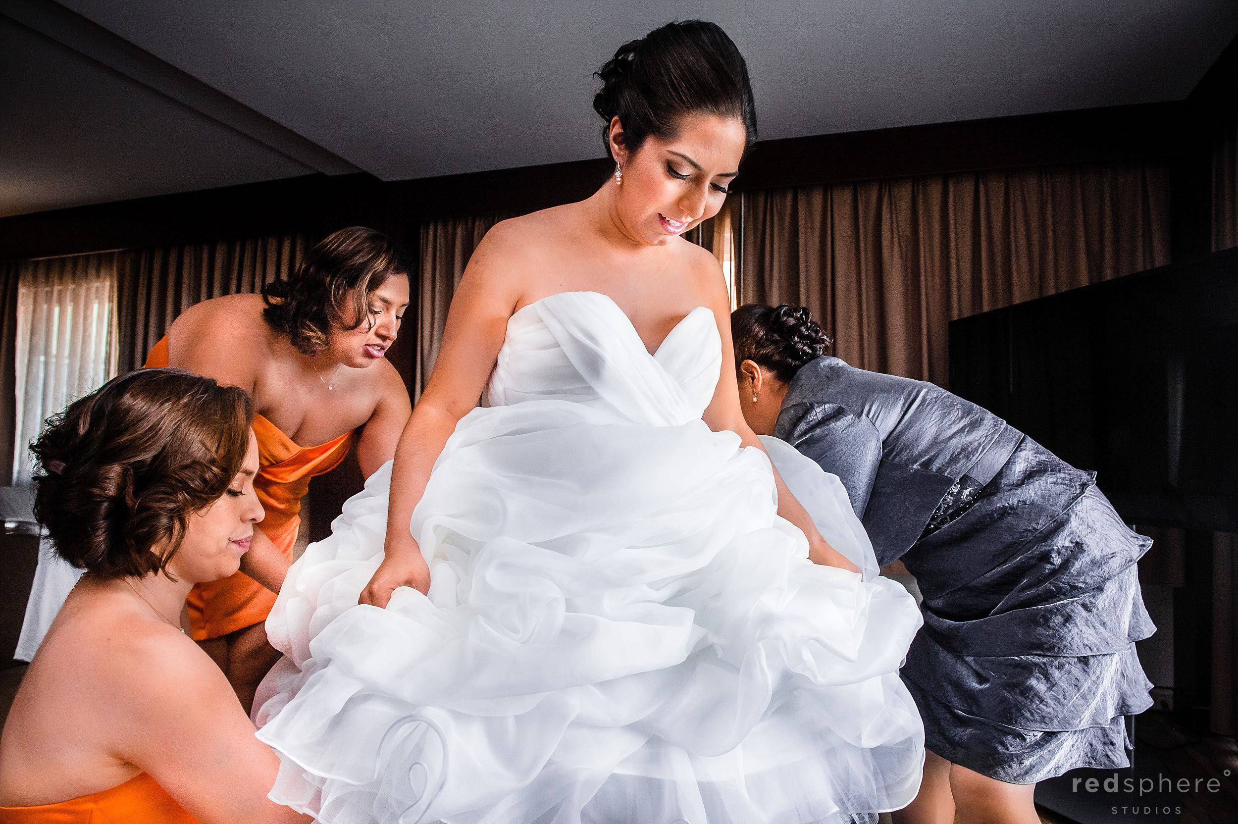 Bridesmaids and Mother Help Bride Into her Wedding Gown