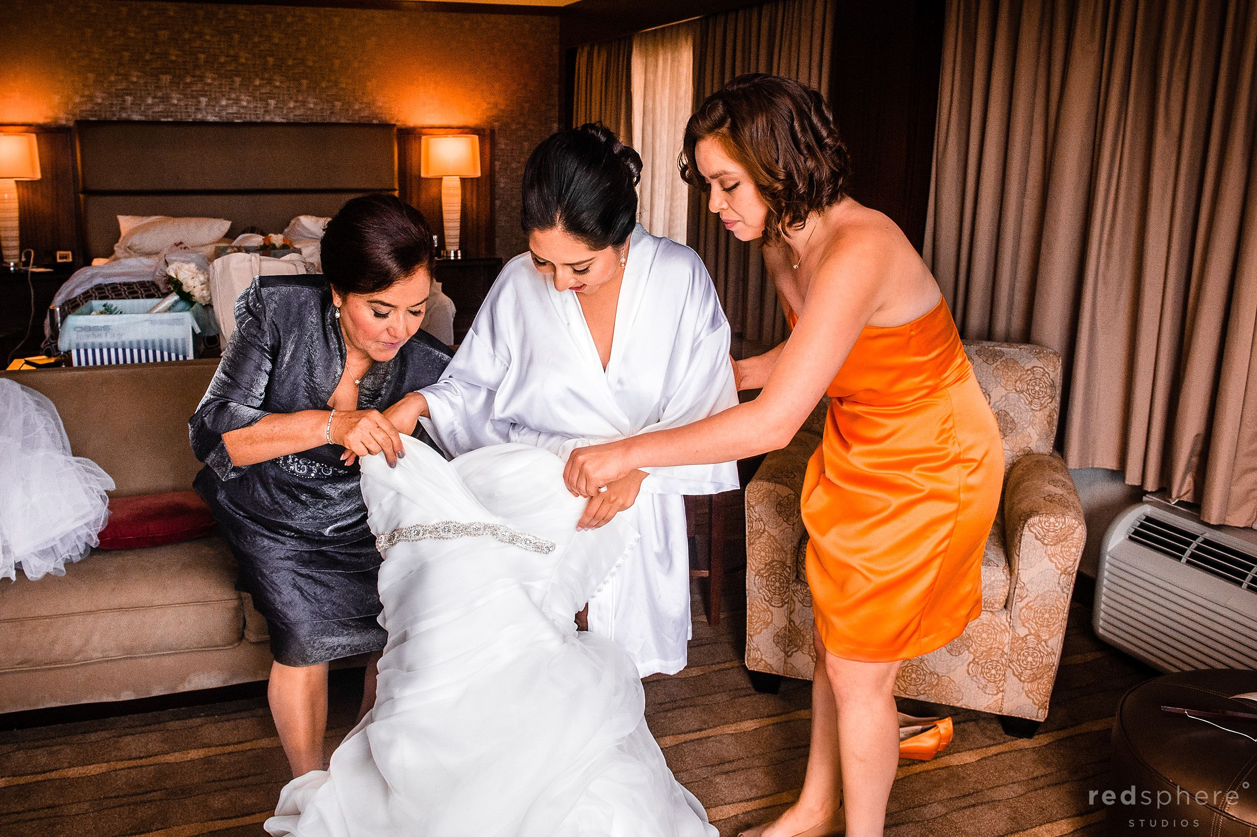 Bridesmaid and Mother of Bride Helping Bride put on Dress