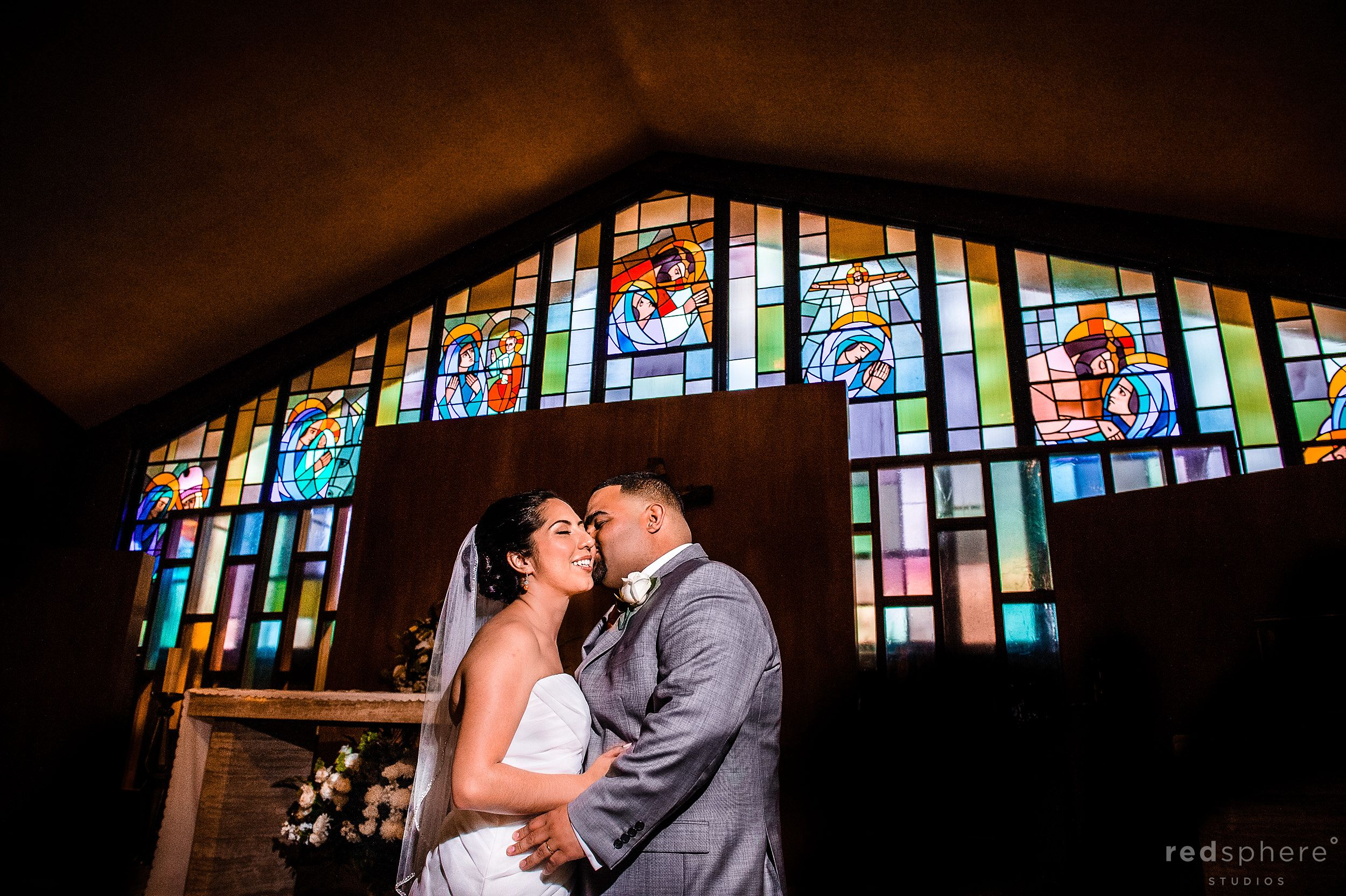 Groom Kisses Bride With Stained Glass Background