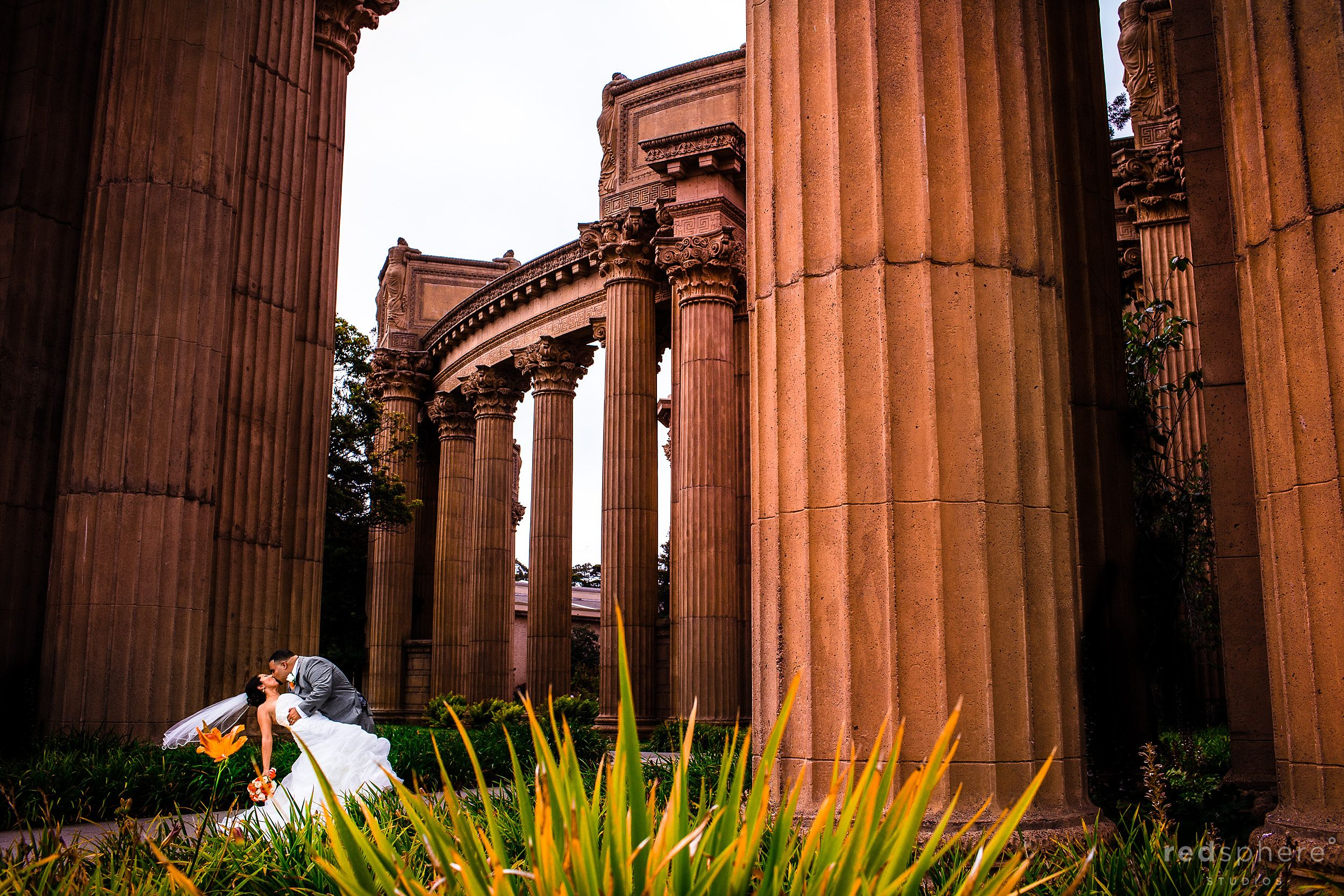 Bride and Groom Kiss Surrounded by Palace of Fine Arts Pillars