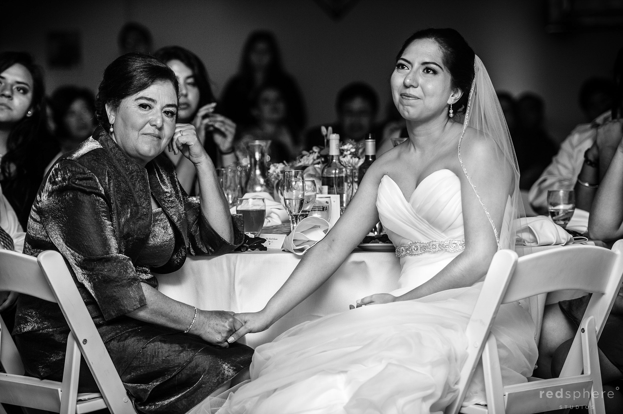Bride and Mother Hold Hands at Wedding Reception