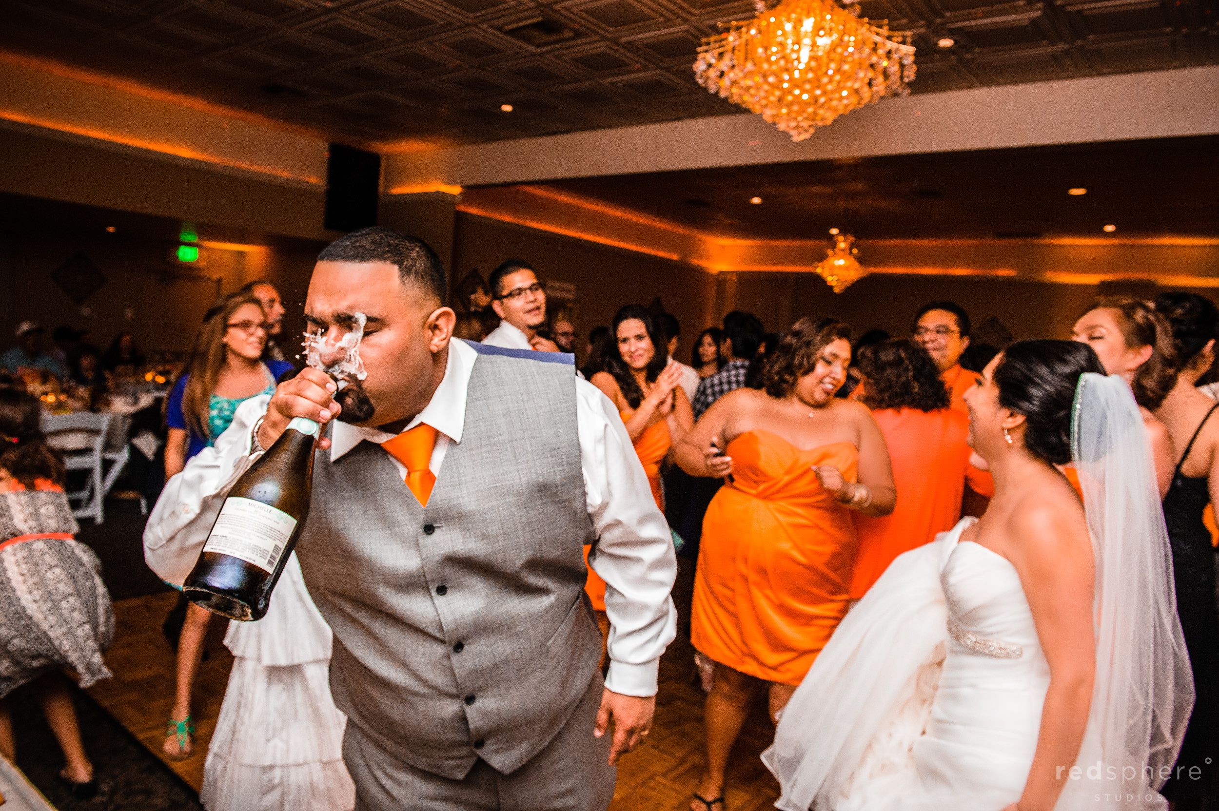 Groom Popping Champagne Bottle With Bride and Bridesmaids