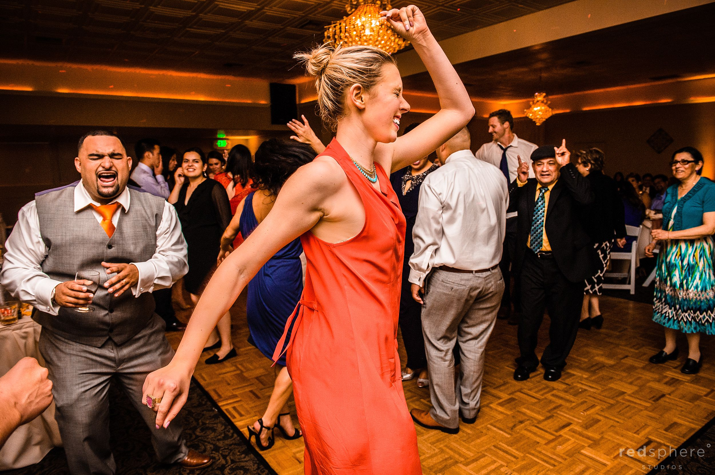Guests Dancing and Groom Appearing in the Background