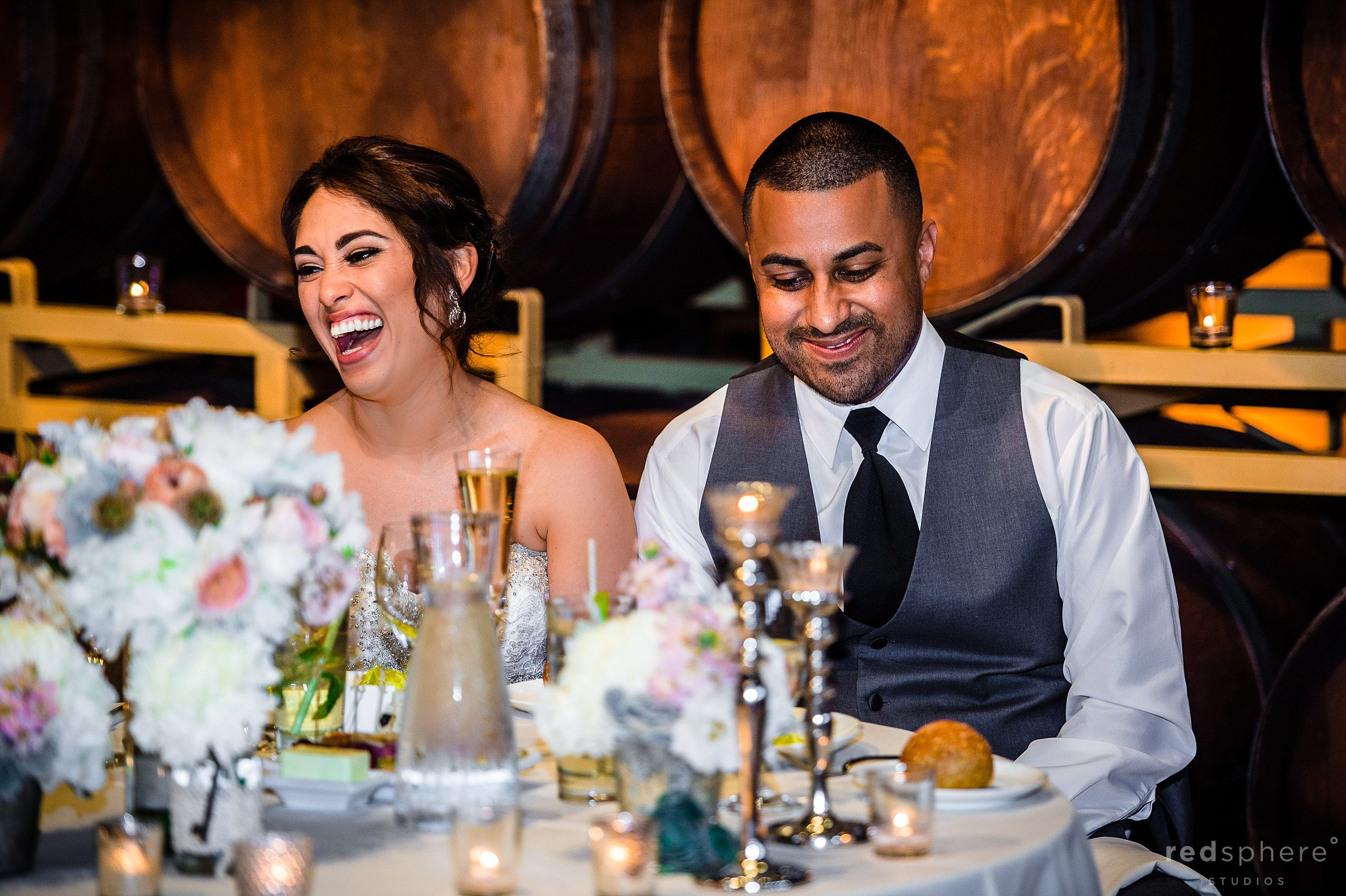 Newly Wed Bride and Groom Laughing at Reception Table