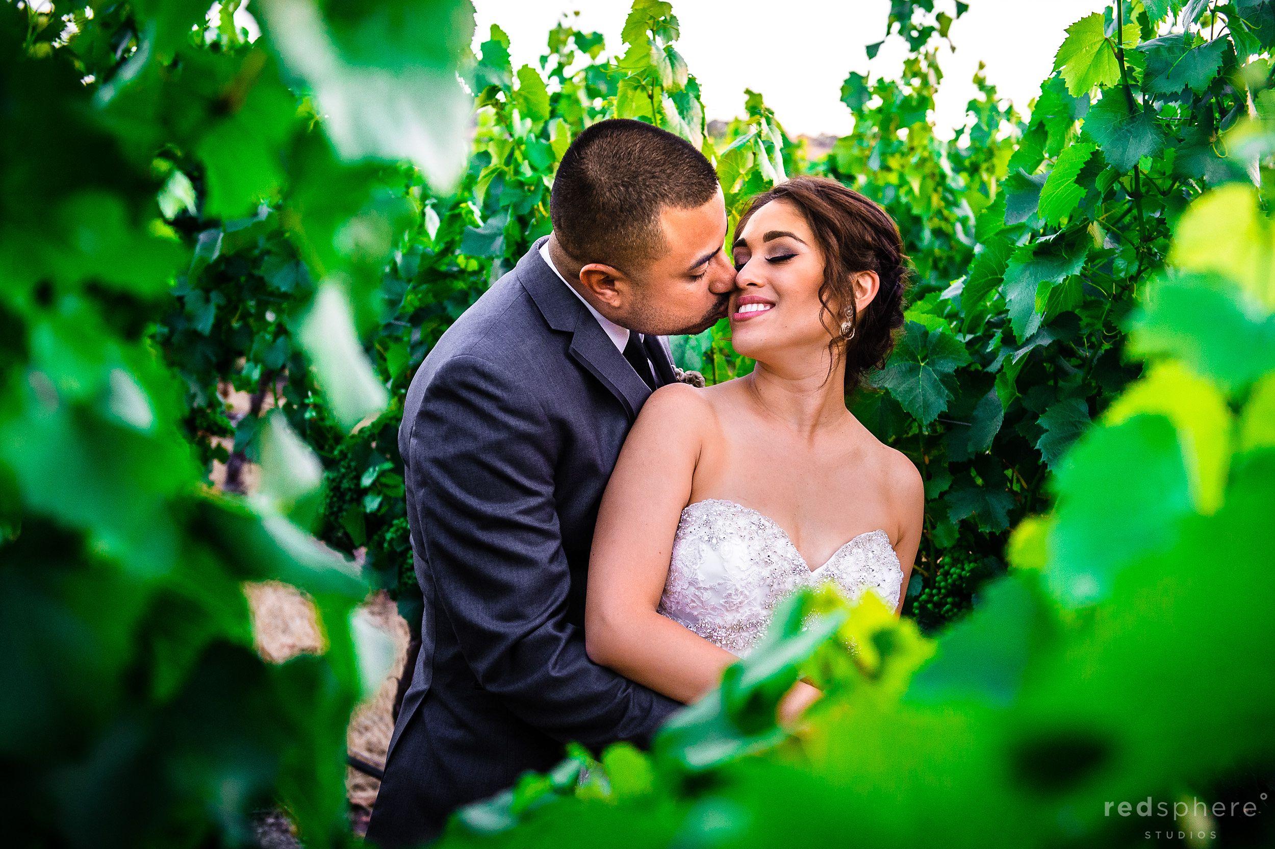 Groom Gives Bride a Soft Kiss Palm Event Center
