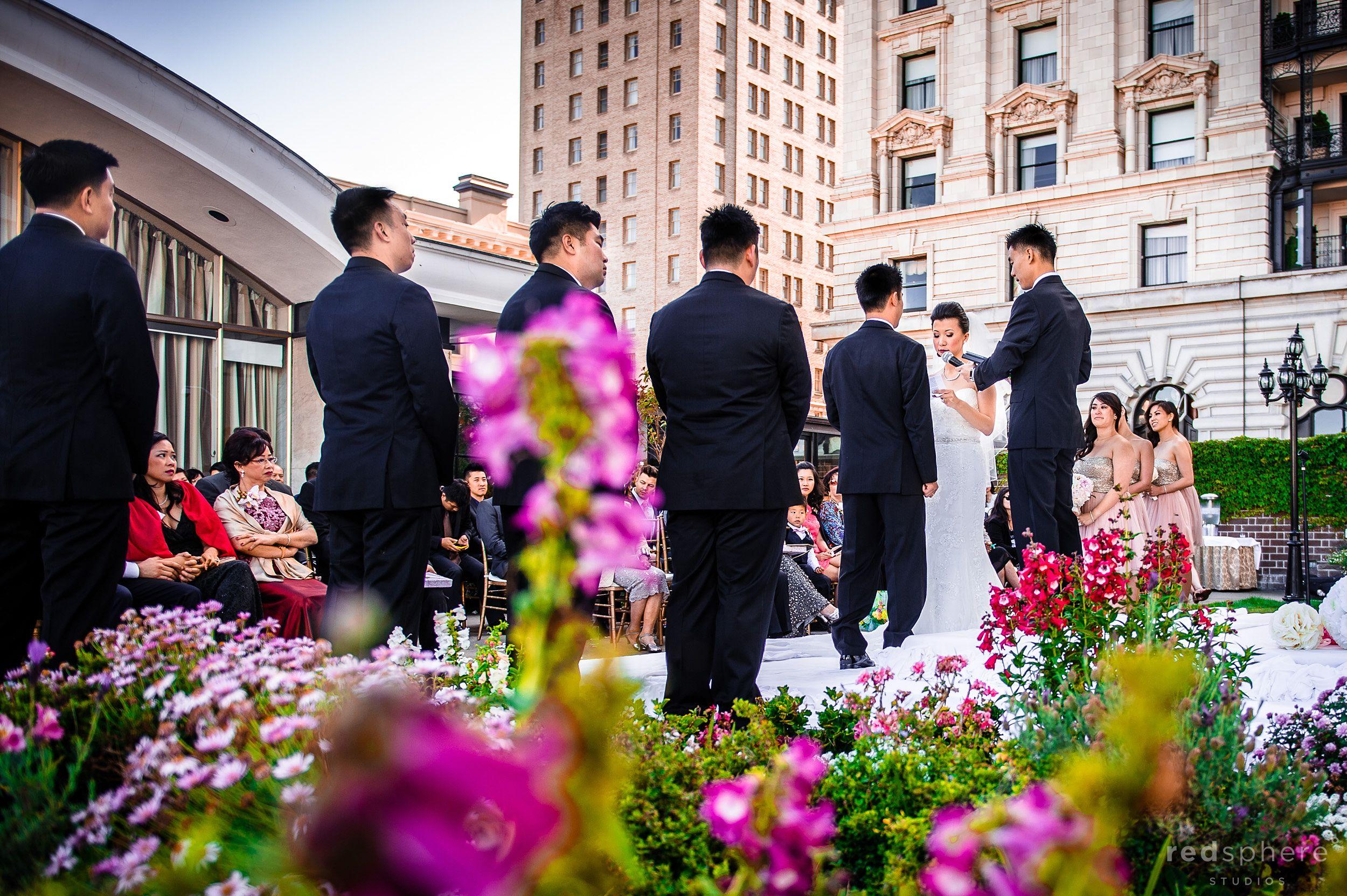 Bride, Groom, Bridemaids', and Groomsmen Behind Fairmont Hotel's Flowers