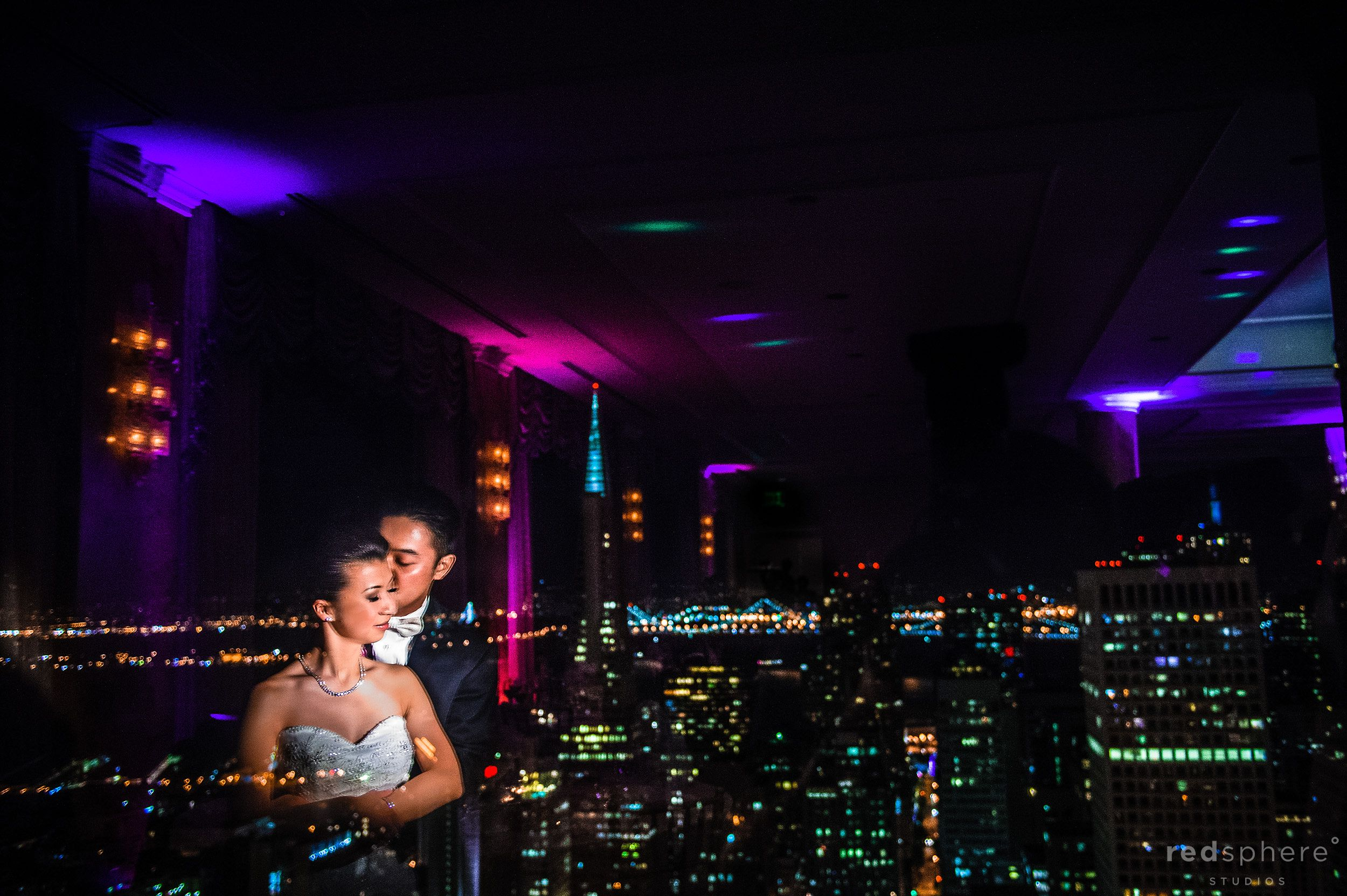 Unique Lighting Shot of Bride and Groom While Night Hits San Francisco City From Fairmont Hotel