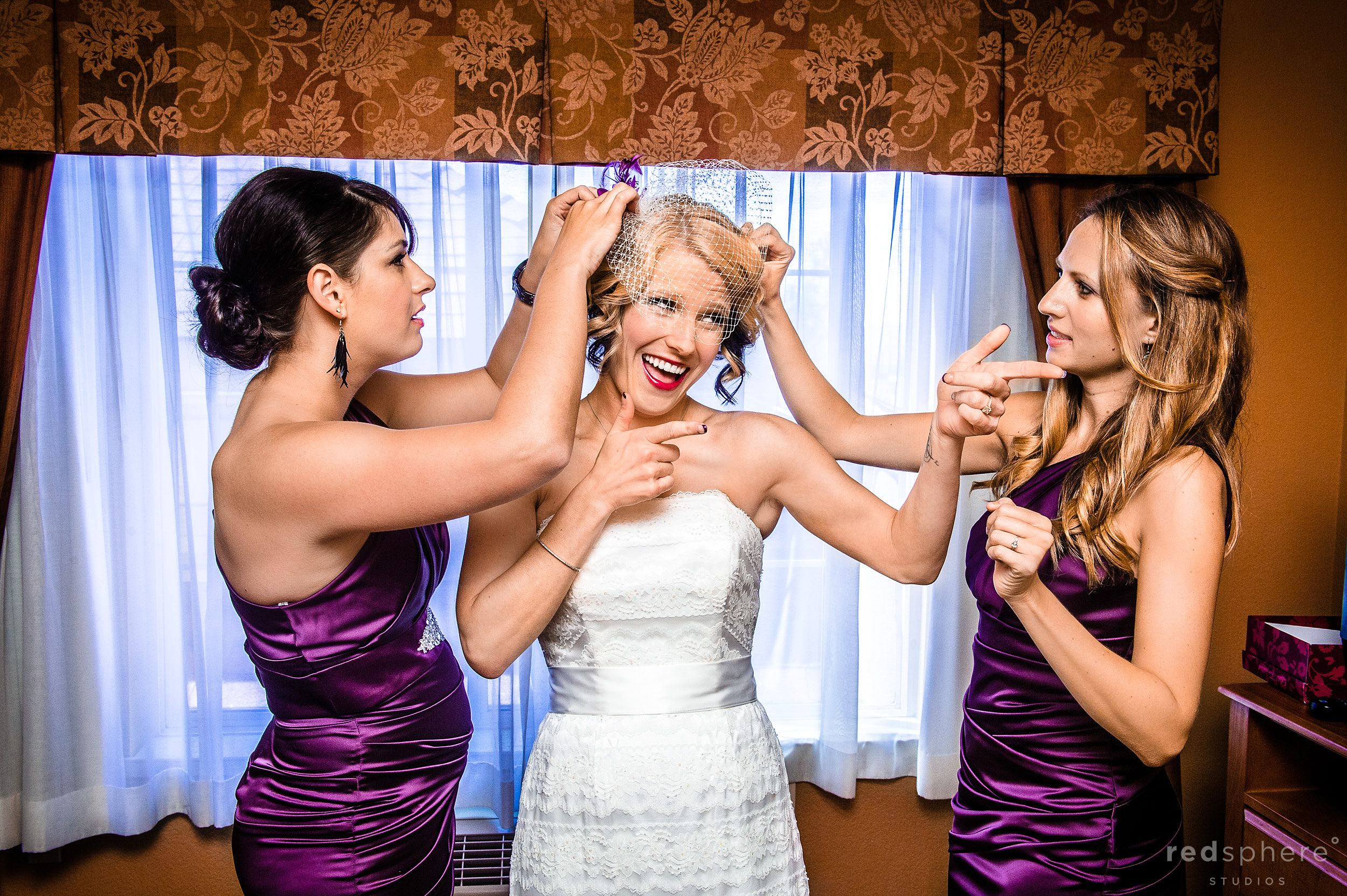 Bridesmaid Fixing Bride's Hair As She Winks at Friends