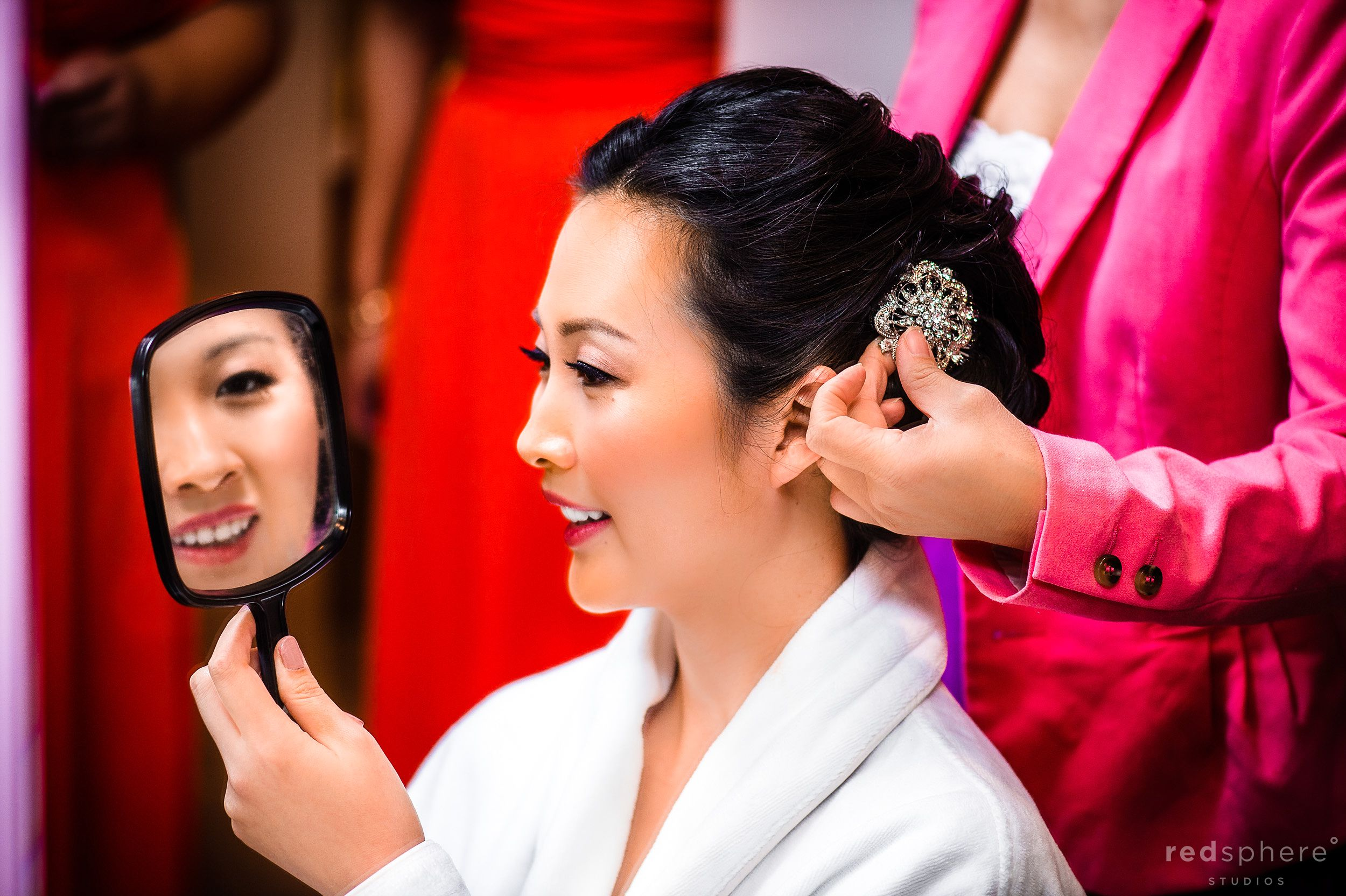 Bride Looks Into Mirror With Amazement As Mothers Adds Silver Clip Into Hair
