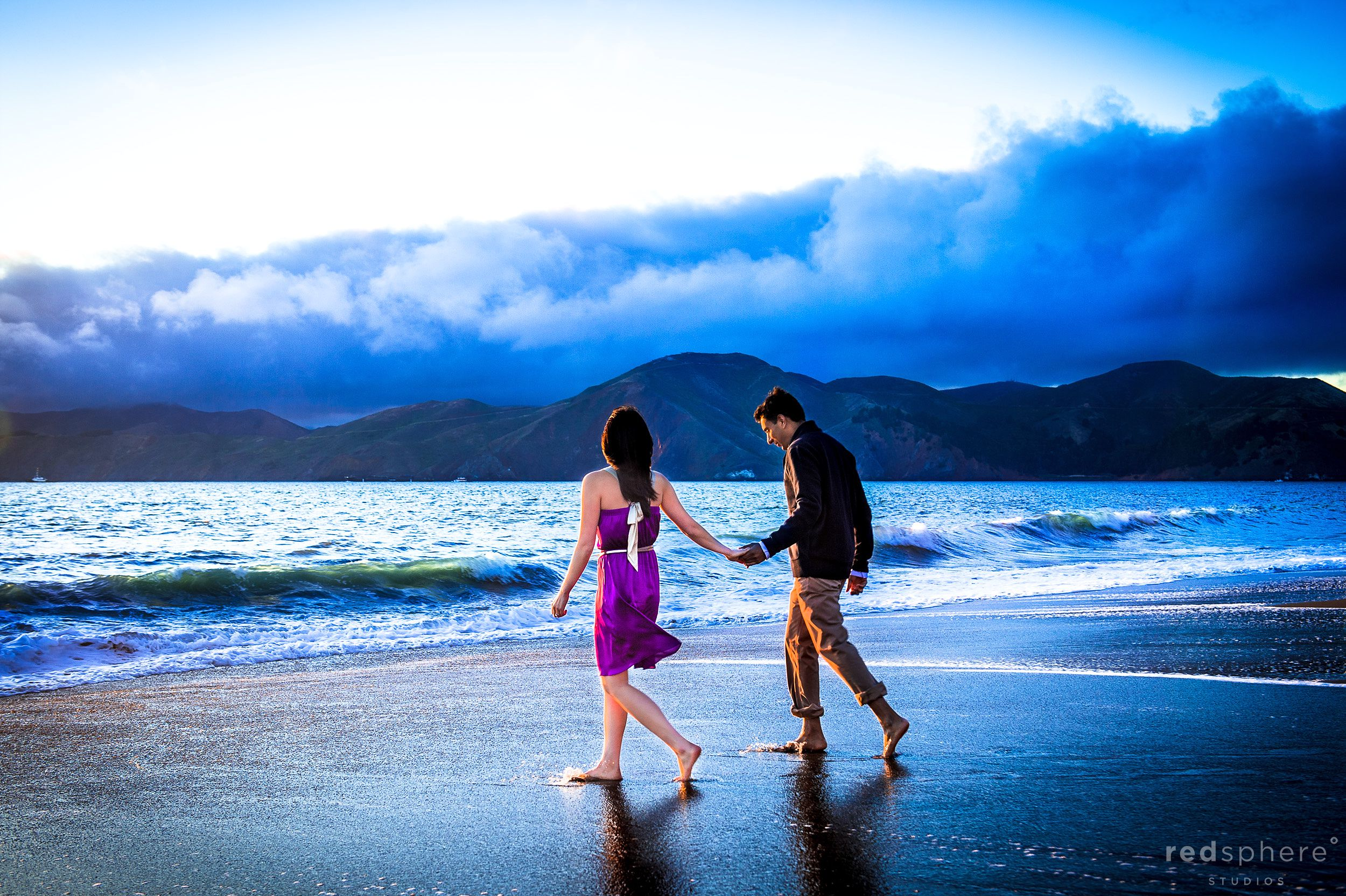 Couple Stroll on Beach, Stormy Clouds Along Baker Beach