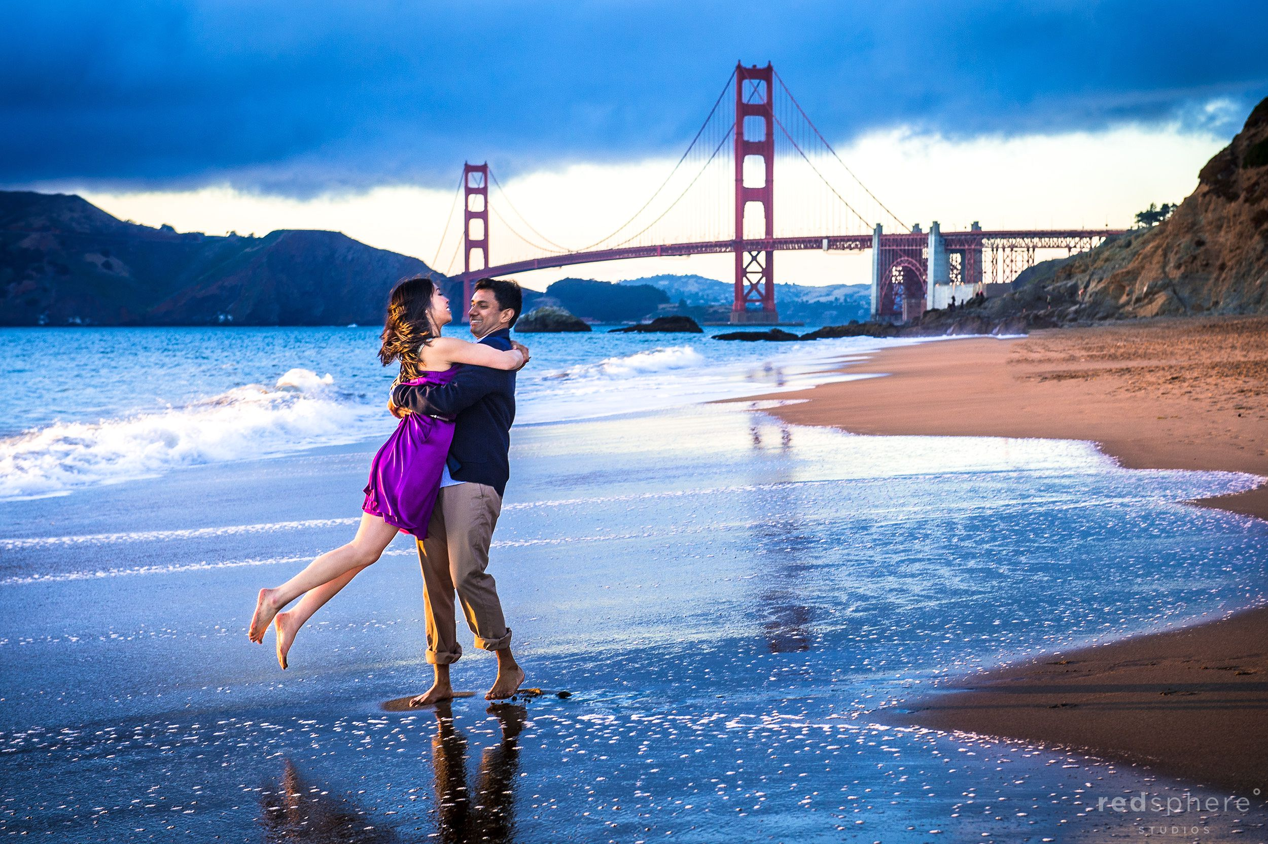 Man Carries Woman on Shoreline of Baker Beach, Cute Engagement Moments