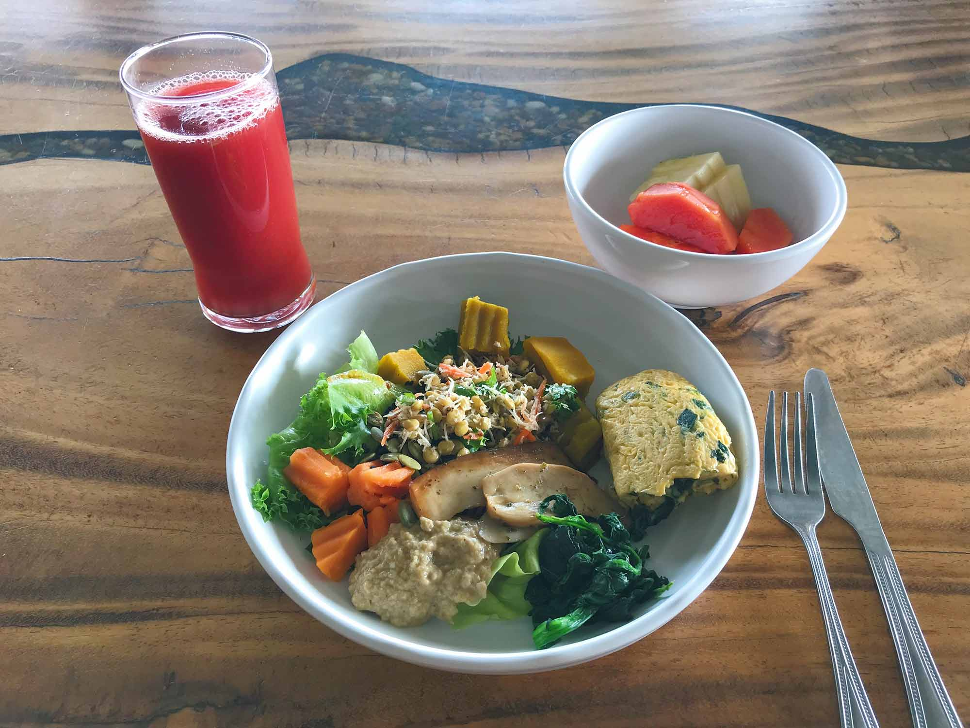 Breakfast salad of mung beans, oyster mushrooms, veggie dip, sweet potatoes, and spinach. A side of veggie omelet, fresh fruit, and beetroot ginger juice.