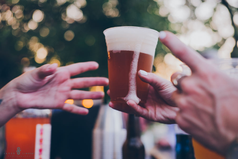Beer being passed off to wedding guest at Texas wedding reception