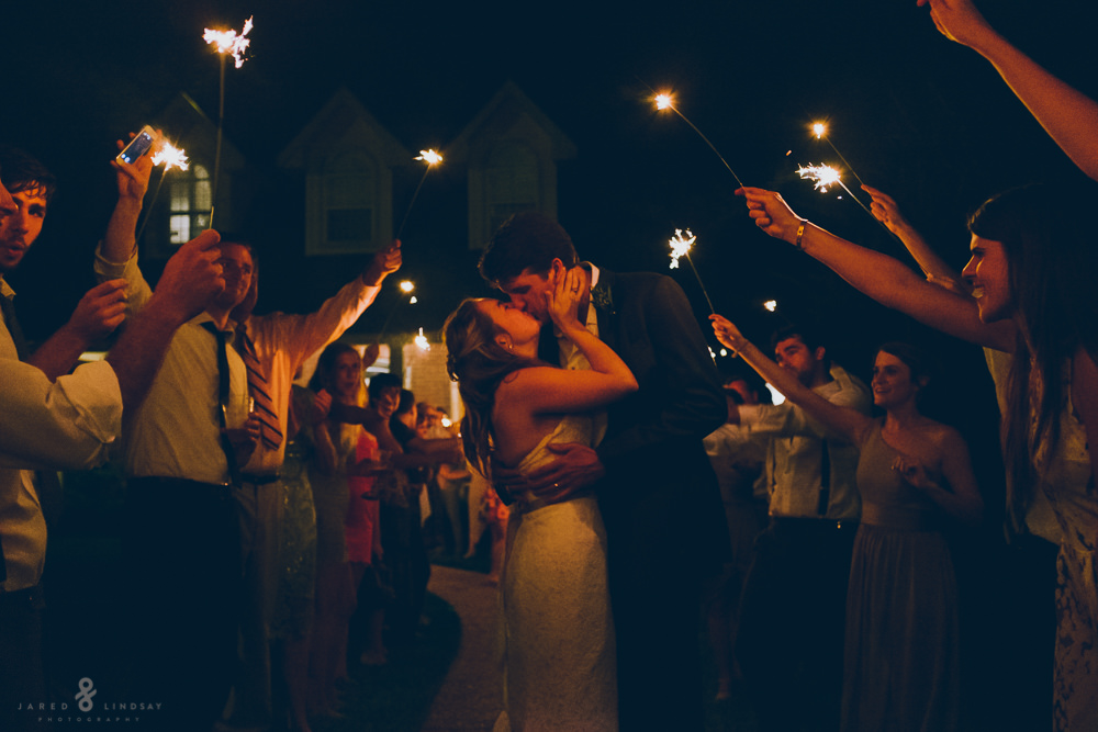 Bride and groom kissing under sparklers during exit
