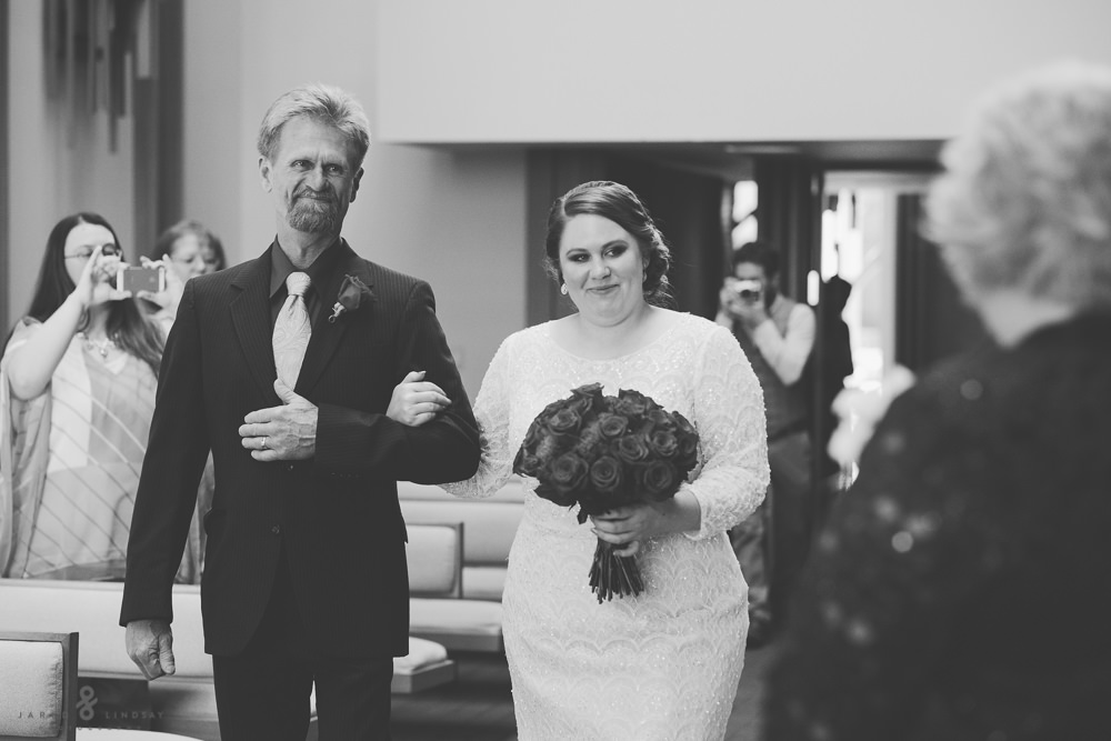 Father and bride walking down isle at wedding