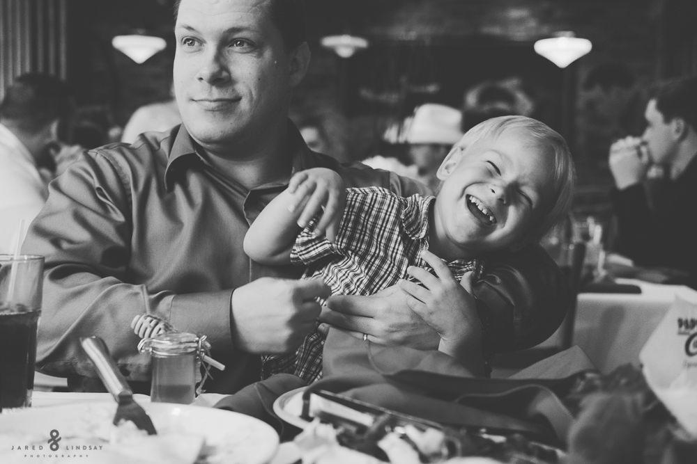 Dad tickling boy during wedding reception