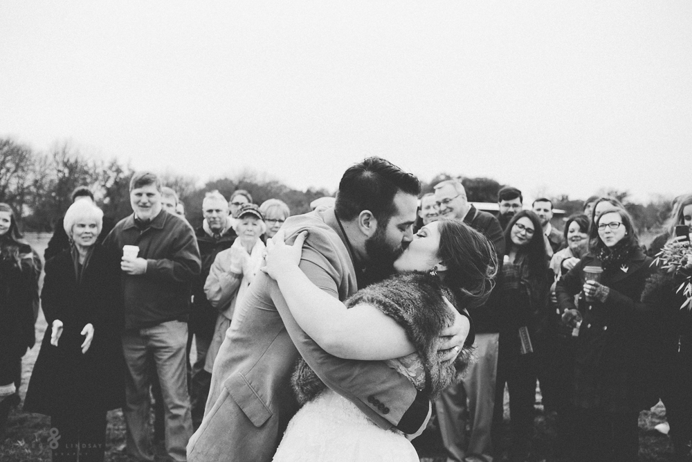 Bride and groom kissing in front of guests at ceremony