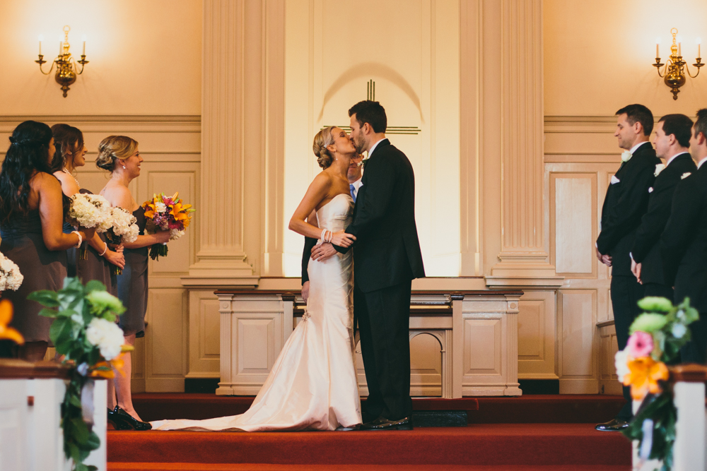 Bride and groom kissing during wedding at TCU chapel