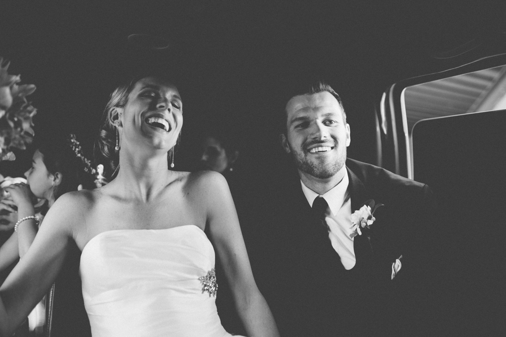 Groom and bride laughing wile riding in back of limousine