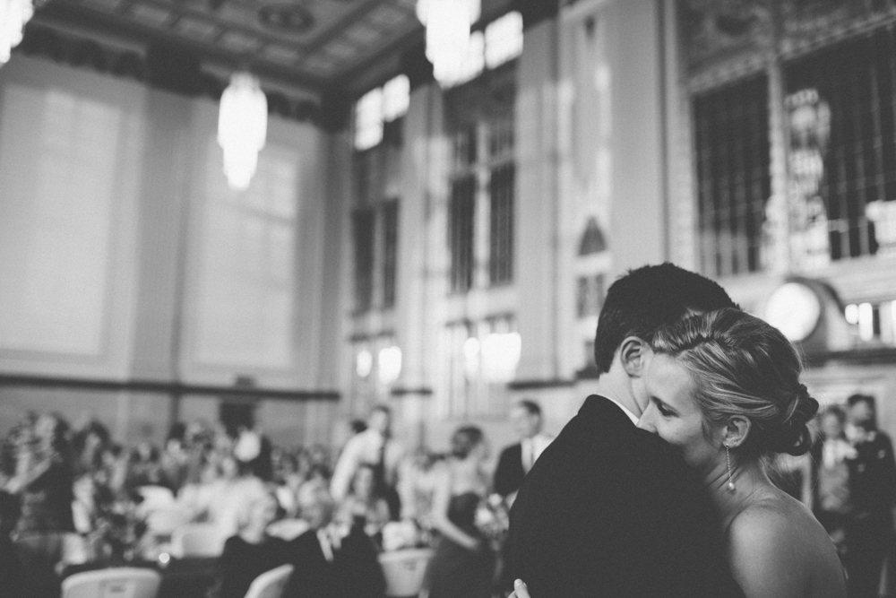 Bride with head on shoulder of groom during first dance at wedding reception