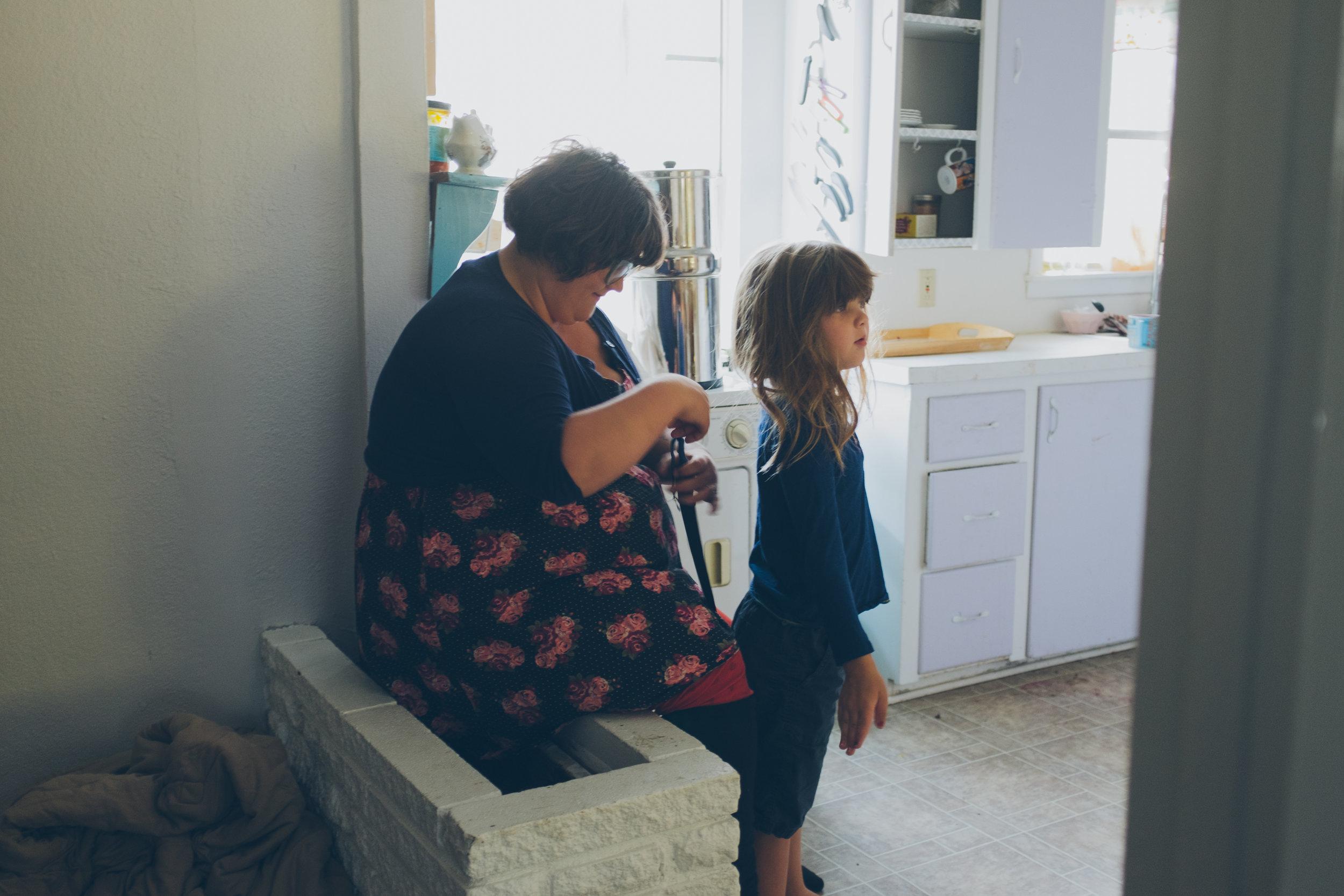 Mother helping dress little boy.