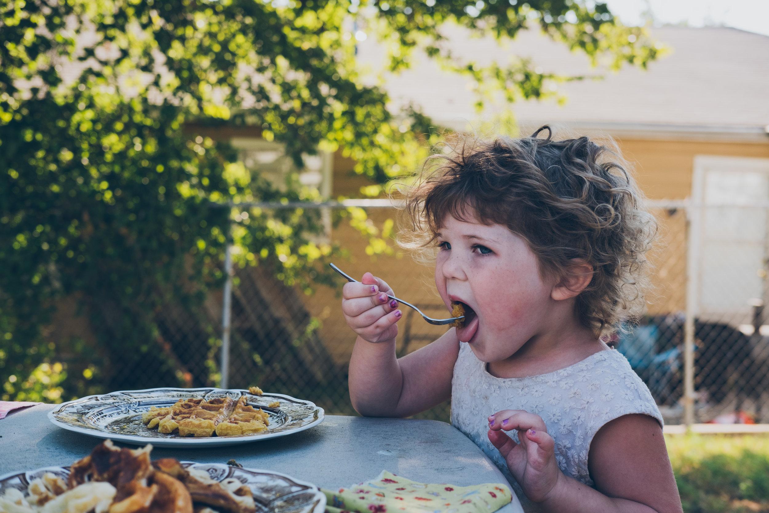 Little girl eating waffles