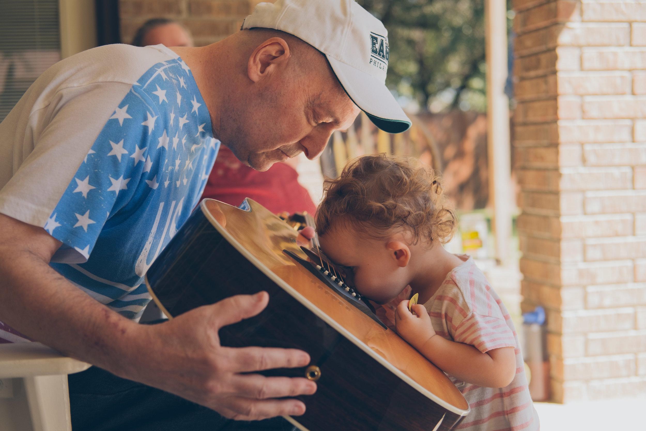 Old man and baby looking at guitar