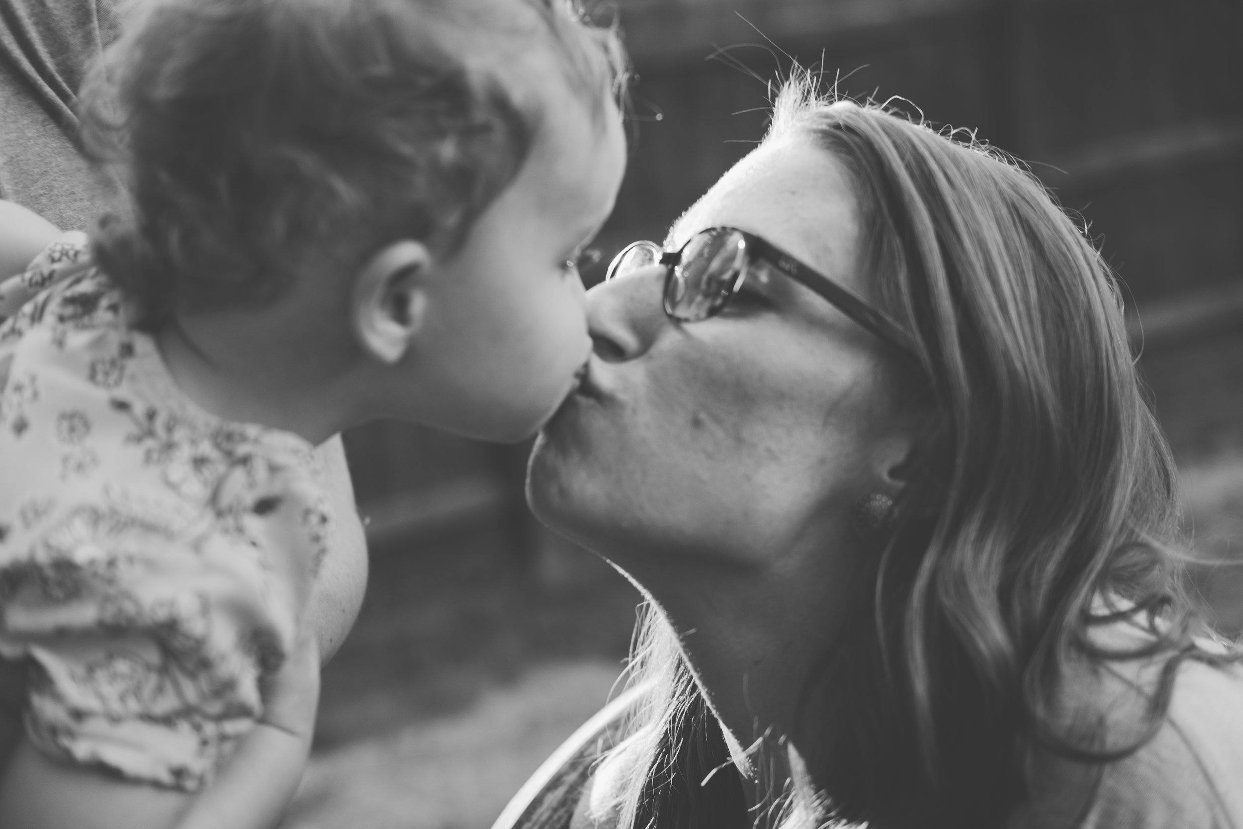 Woman with glasses kissing young child