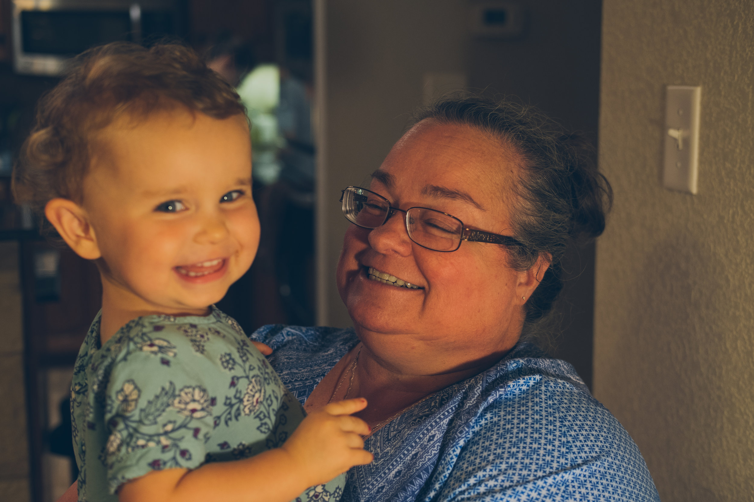 Woman with glasses holding small child smiling