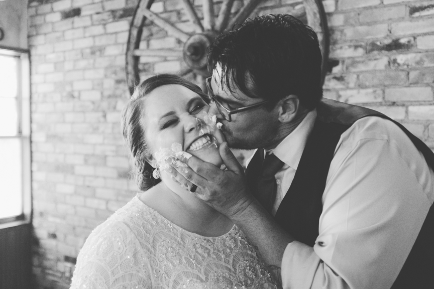 Groom kissing bride with cake on her face during wedding reception