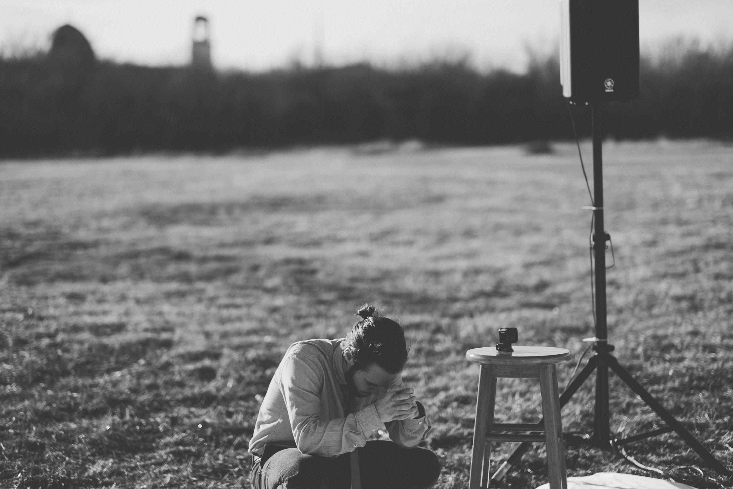 Man kneeling in prayer hands clasped together