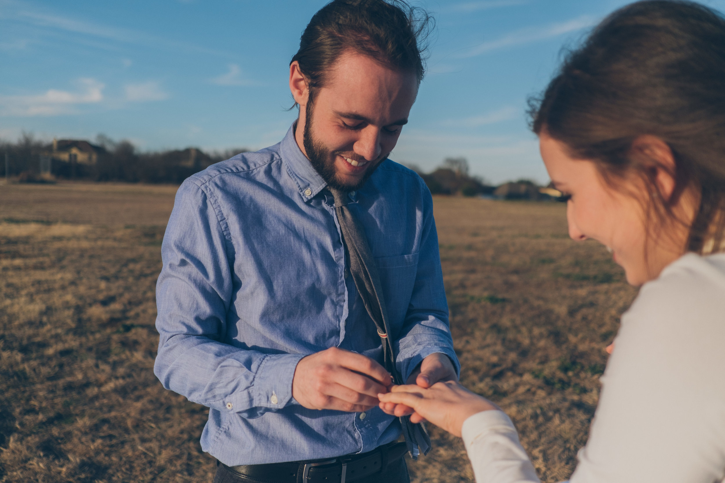 Man in blue shirt placing engagement ring on hand of woman