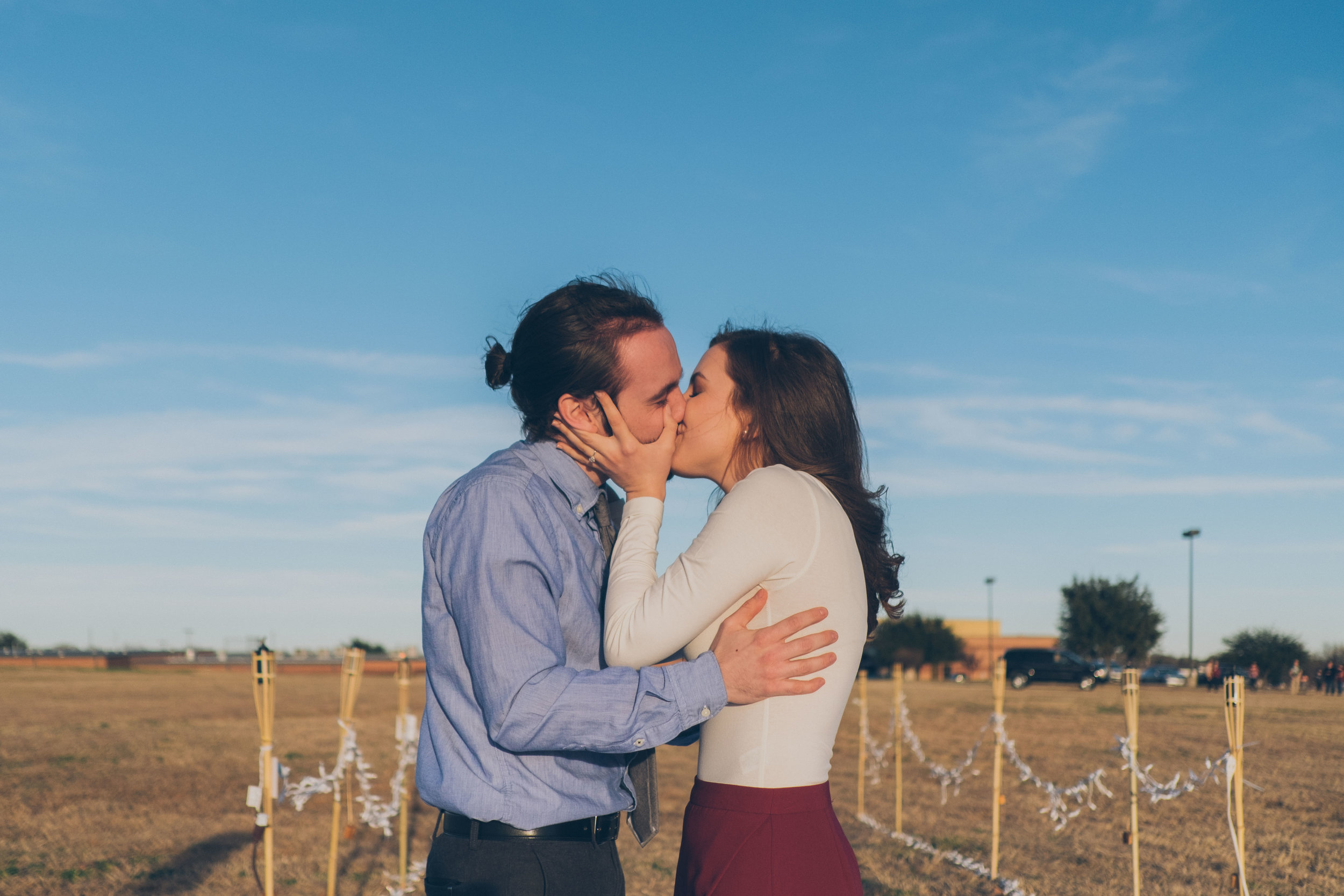 Man and woman kissing with blue sky in background