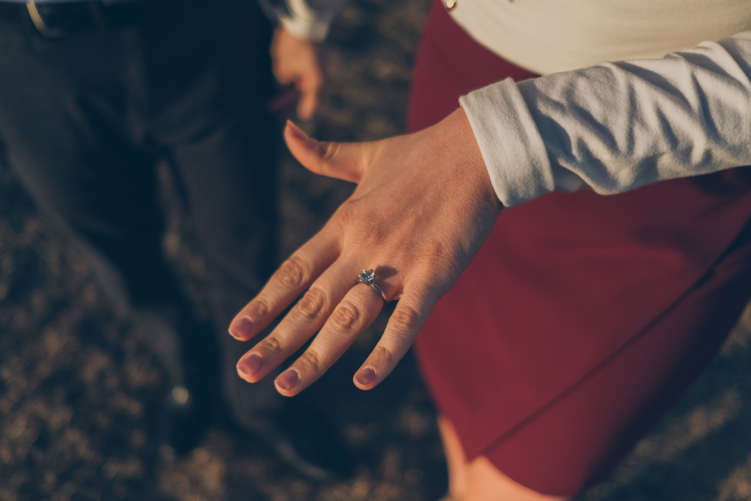 Woman's left hand from above showing engagement ring.