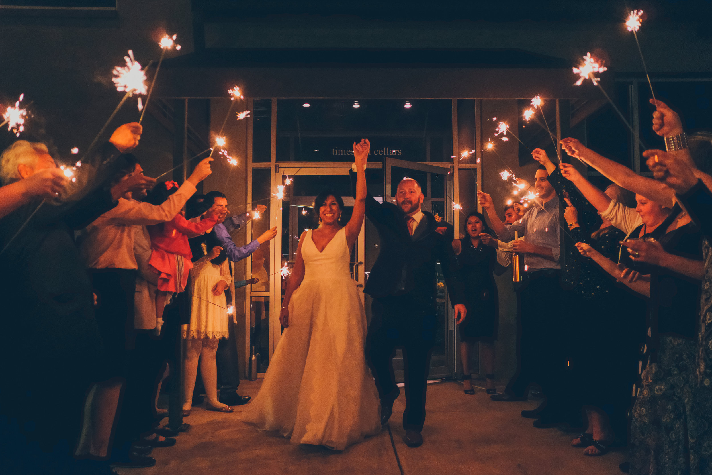 Bride and groom exiting the venue with hands raised while surrounded by sparklers at night time.