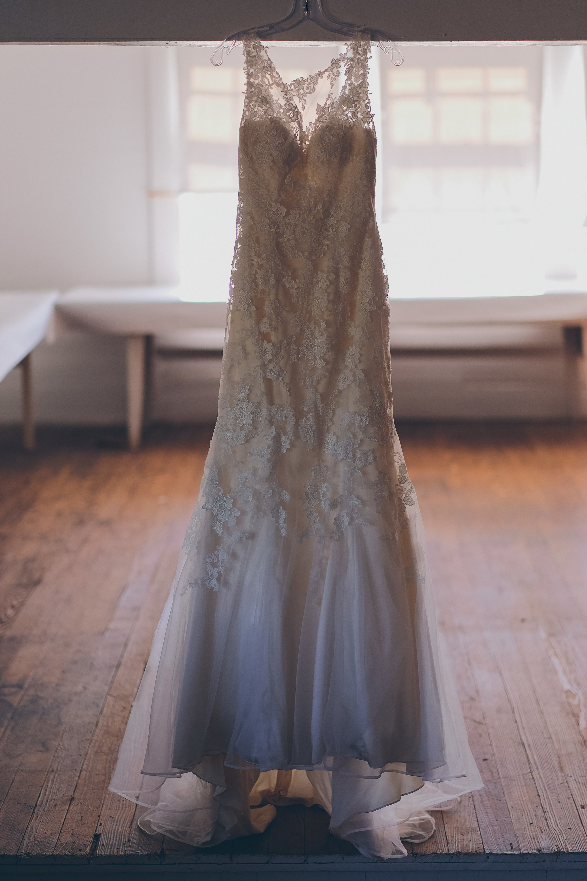 Wedding dress hanging in middle of empty room