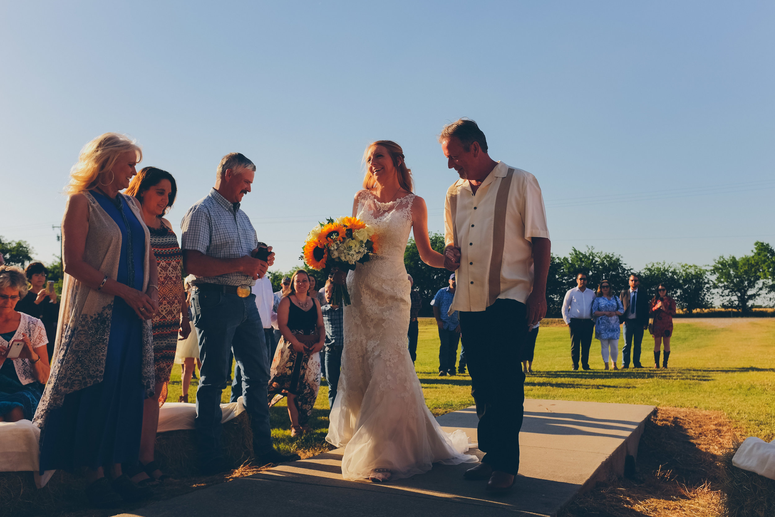 Bride and her father walking down the isle in outdoor country wedding.