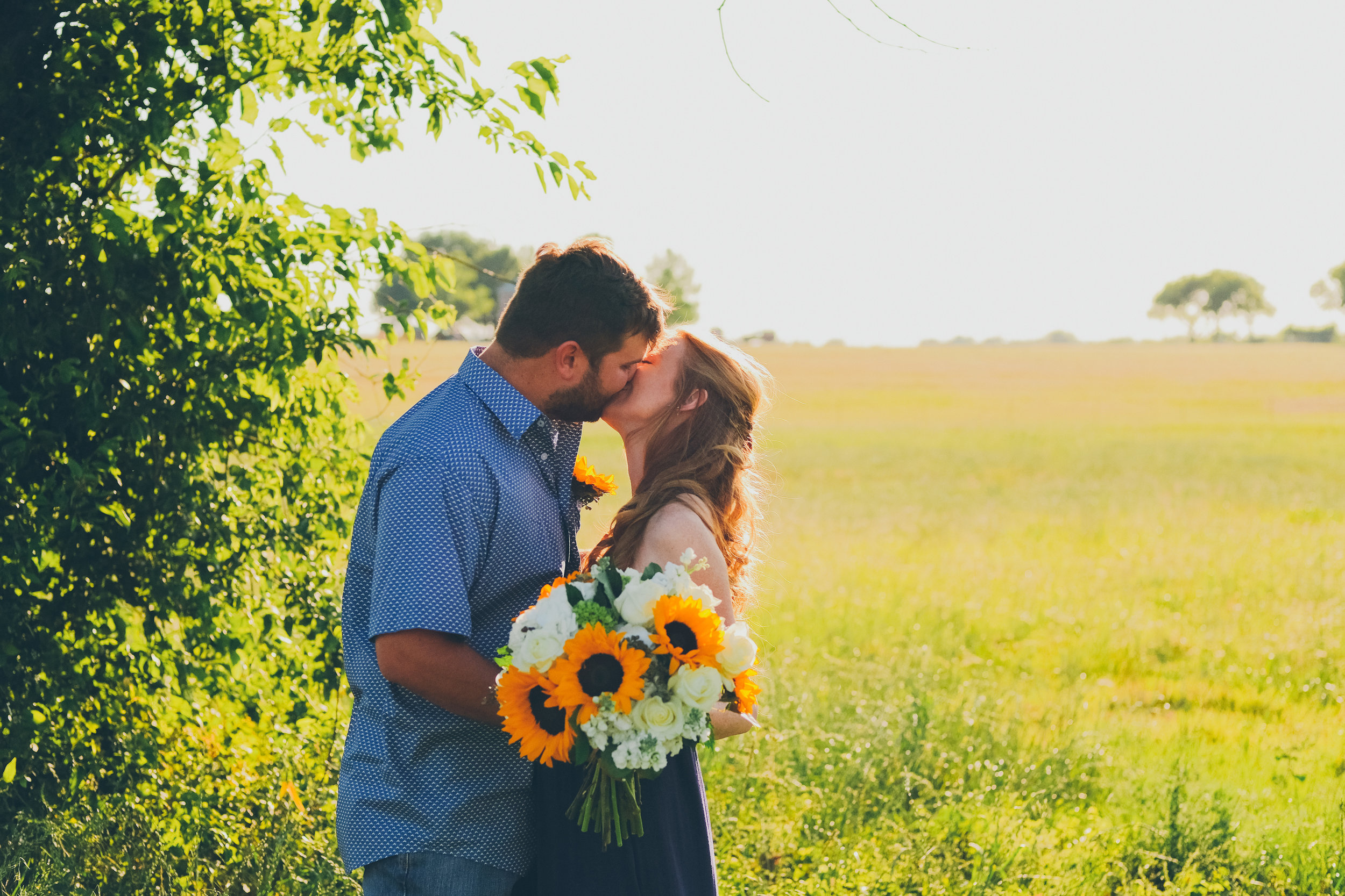 Color photo of bride and groom kissing in a field.