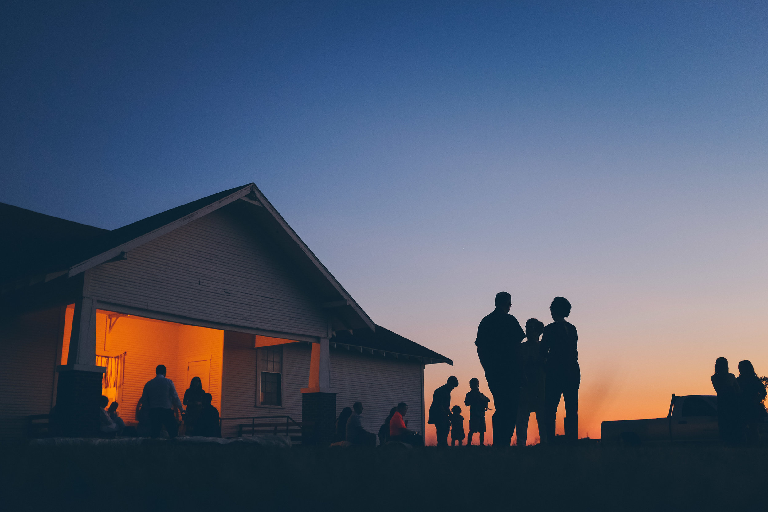 Color photo, outside wedding venue, silhouette of guests at sunset.