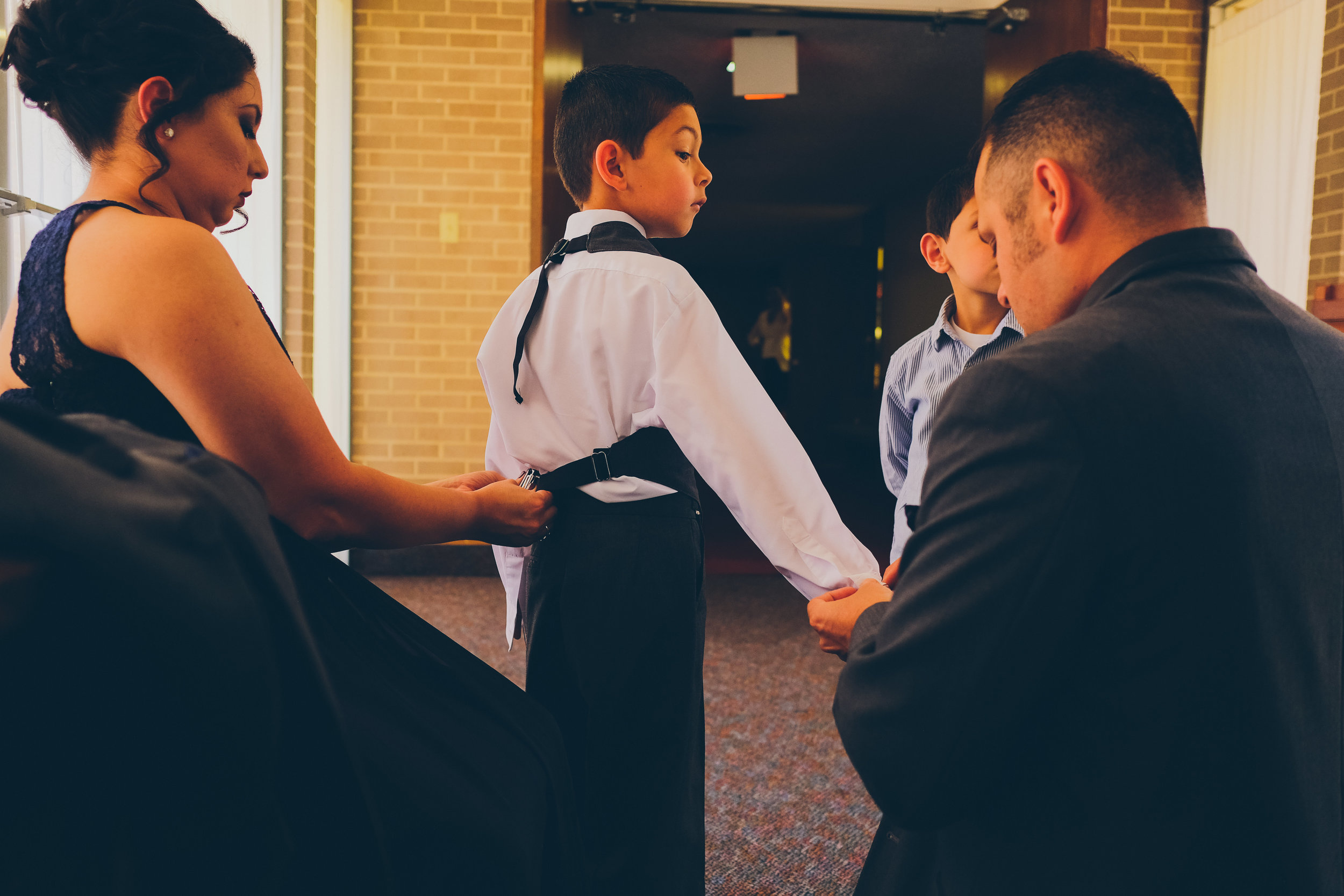 Color photo of boy being dressed by his parents before wedding